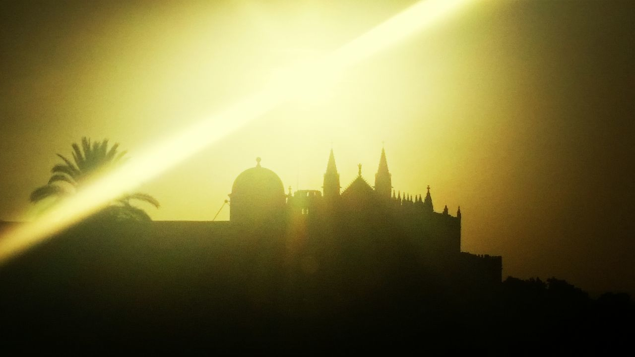 architecture, lens flare, building exterior, sun, silhouette, sunlight, built structure, history, sunset, religion, outdoors, spirituality, clear sky, no people, sky, nature, city, day