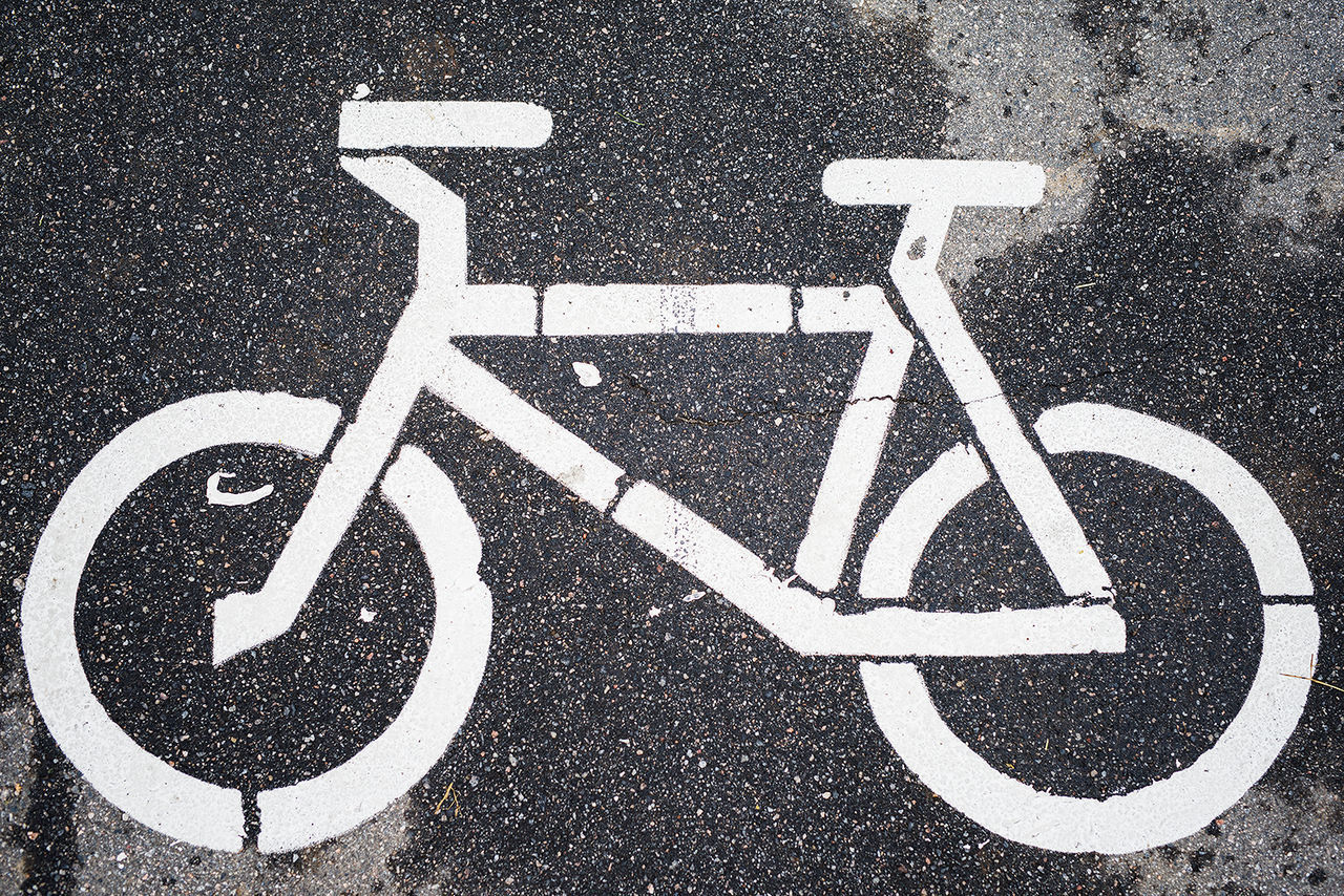 road, road sign, transportation, road marking, street, guidance, bicycle lane, white color, safety, human representation, bicycle, communication, outdoors, asphalt, symbol, high angle view, day, parking sign, no people, differing abilities, wheelchair access