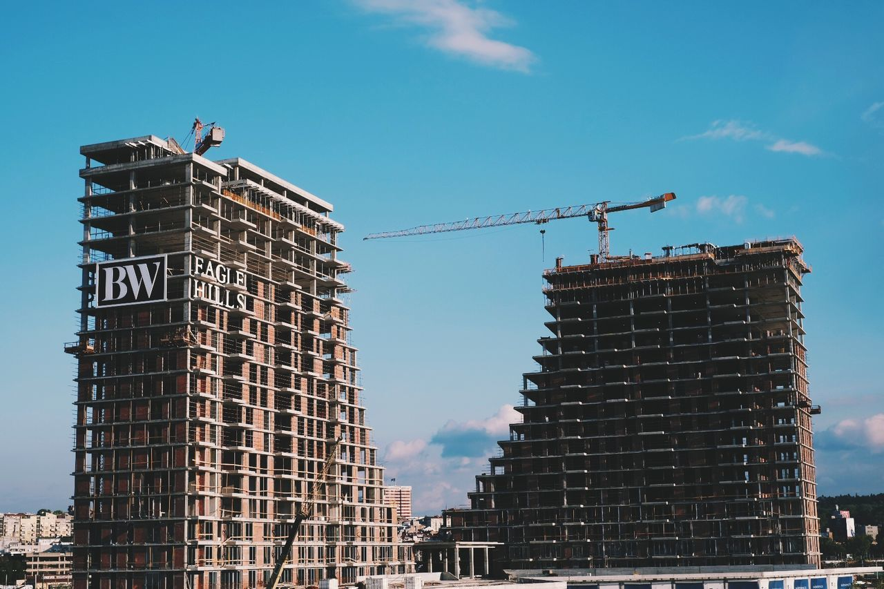construction site, architecture, development, low angle view, built structure, crane - construction machinery, construction, manual worker, day, building - activity, building exterior, construction worker, working, outdoors, occupation, sky, real people, progress, men, city, people