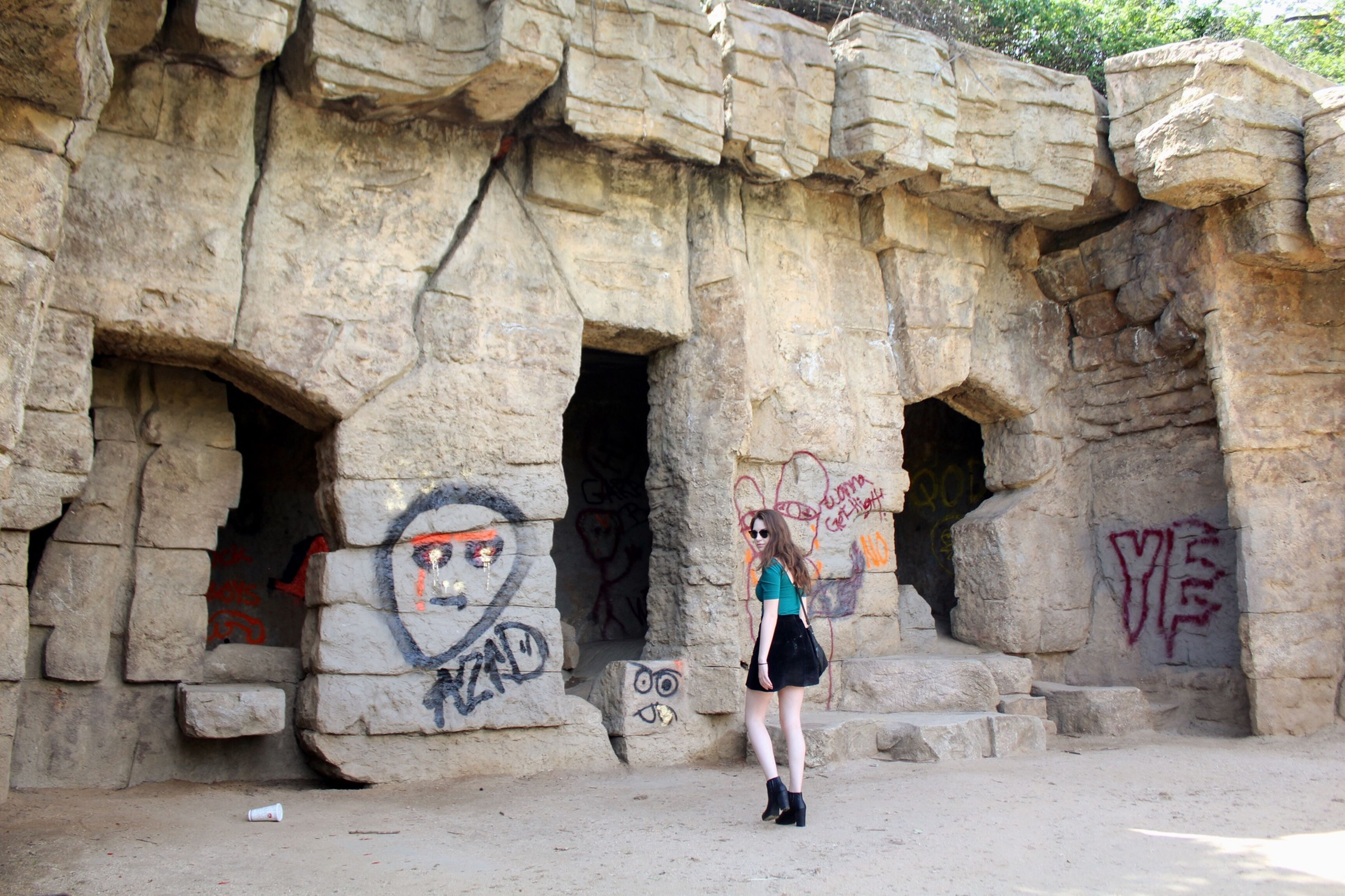 architecture, built structure, graffiti, full length, lifestyles, building exterior, people, wall - building feature, leisure activity, casual clothing, rear view, art, art and craft, walking, wall, text