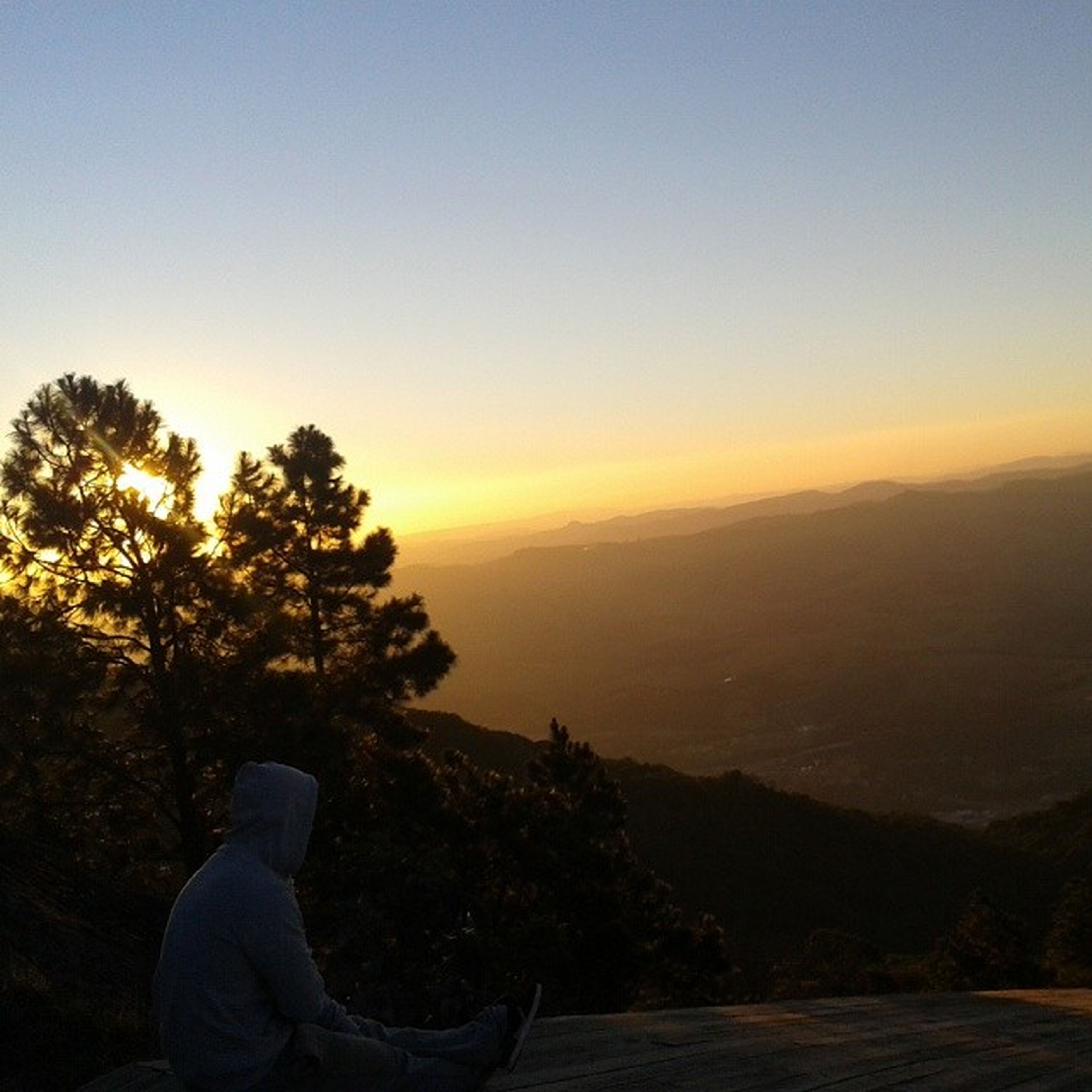 sunset, tranquility, tranquil scene, scenics, beauty in nature, landscape, mountain, silhouette, copy space, clear sky, nature, sky, one person, idyllic, non-urban scene, orange color, tree, remote, mountain range, hill