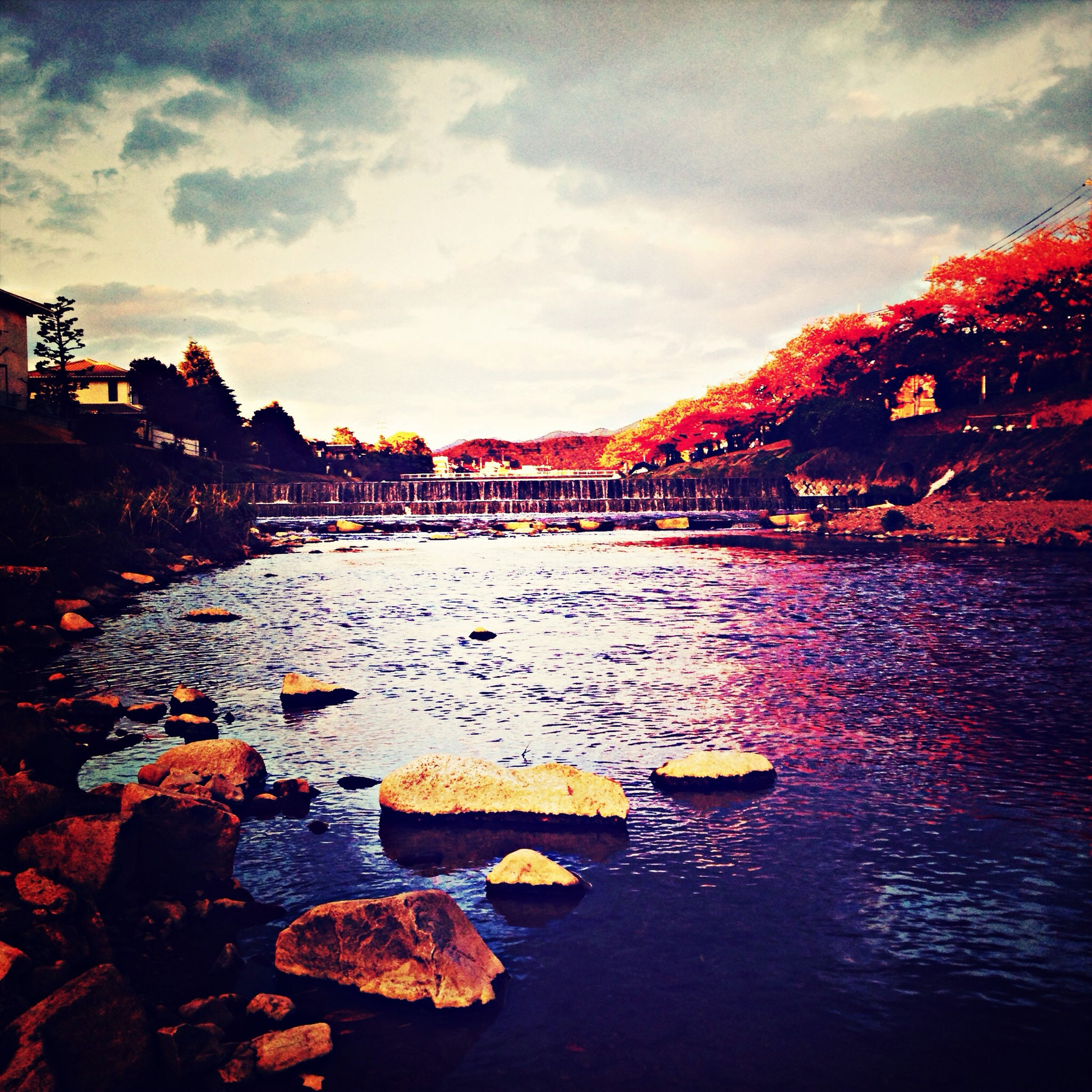 water, sky, architecture, built structure, cloud - sky, building exterior, reflection, river, waterfront, autumn, lake, sunset, cloud, nature, cloudy, outdoors, change, rock - object, beauty in nature, tranquility