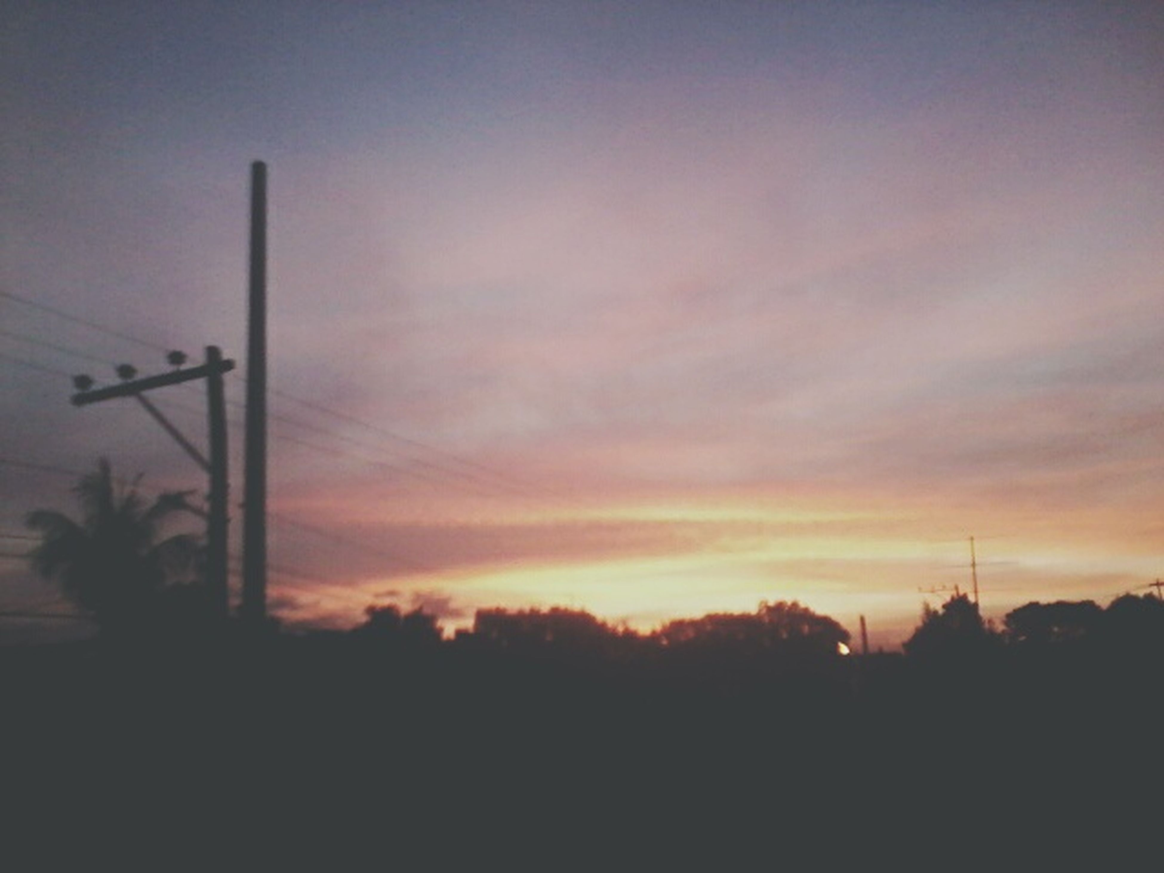 silhouette, sunset, sky, tree, tranquility, beauty in nature, scenics, tranquil scene, electricity pylon, nature, orange color, power line, cloud - sky, low angle view, street light, dusk, electricity, idyllic, connection, no people