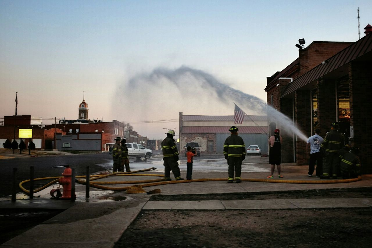 architecture, built structure, building exterior, smoke - physical structure, sky, real people, large group of people, men, outdoors, water, day, women, firefighter, people