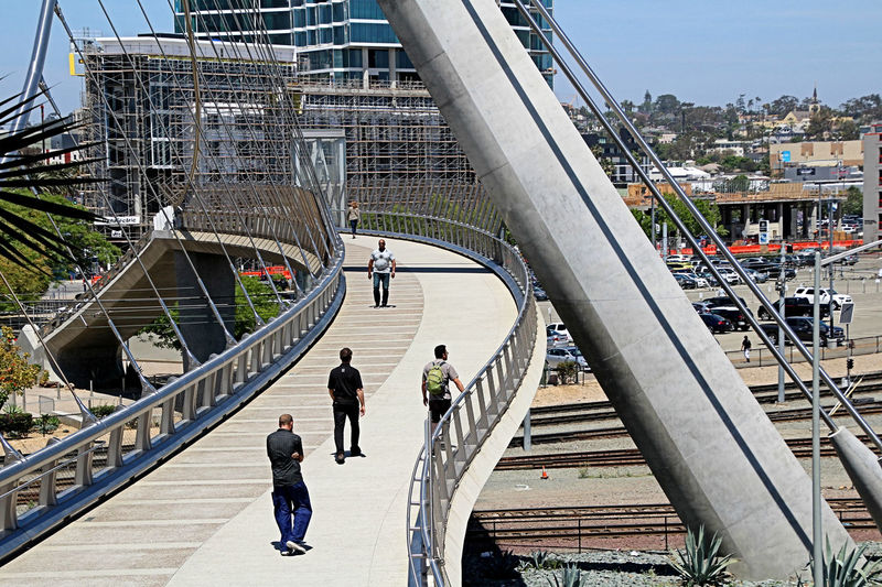 The Harbor Drive pedestrian bridge was completed in March 2011. The bridge was built to accommodate pedestrian traffic from the Petco Park Baseball Stadium crossing to and from parking areas on the opposite side of Harbor Drive at the Bayfront Hotel. The bridge crosses over six lanes of traffic, a rail yard and trolley tracks, and connects the Convention Center with the Gaslamp Quarter and the East Village. It is accessible by stairs and elevators, as seen in these photographs. Bridge, Viaduct, Overpass, Fixed Link, Aqueduct, Join, Link, Connect, Unite; Straddle; Overcome, Reconcile Day Outdoors Pylon, Suspended, Curved Concrete, Self-anchored Pedestrian Bridge, Spire, Cables, Path, San Diego, California, Sky
