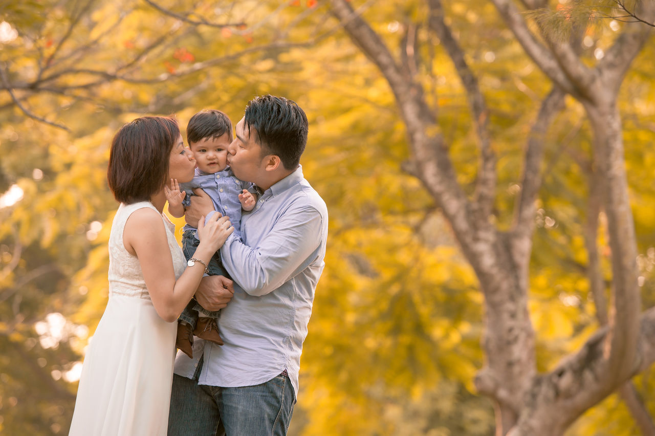 love, togetherness, tree, real people, bonding, embracing, focus on foreground, two people, autumn, outdoors, son, leisure activity, park - man made space, nature, day, lifestyles, childhood, young women, standing, happiness, beauty in nature, young adult