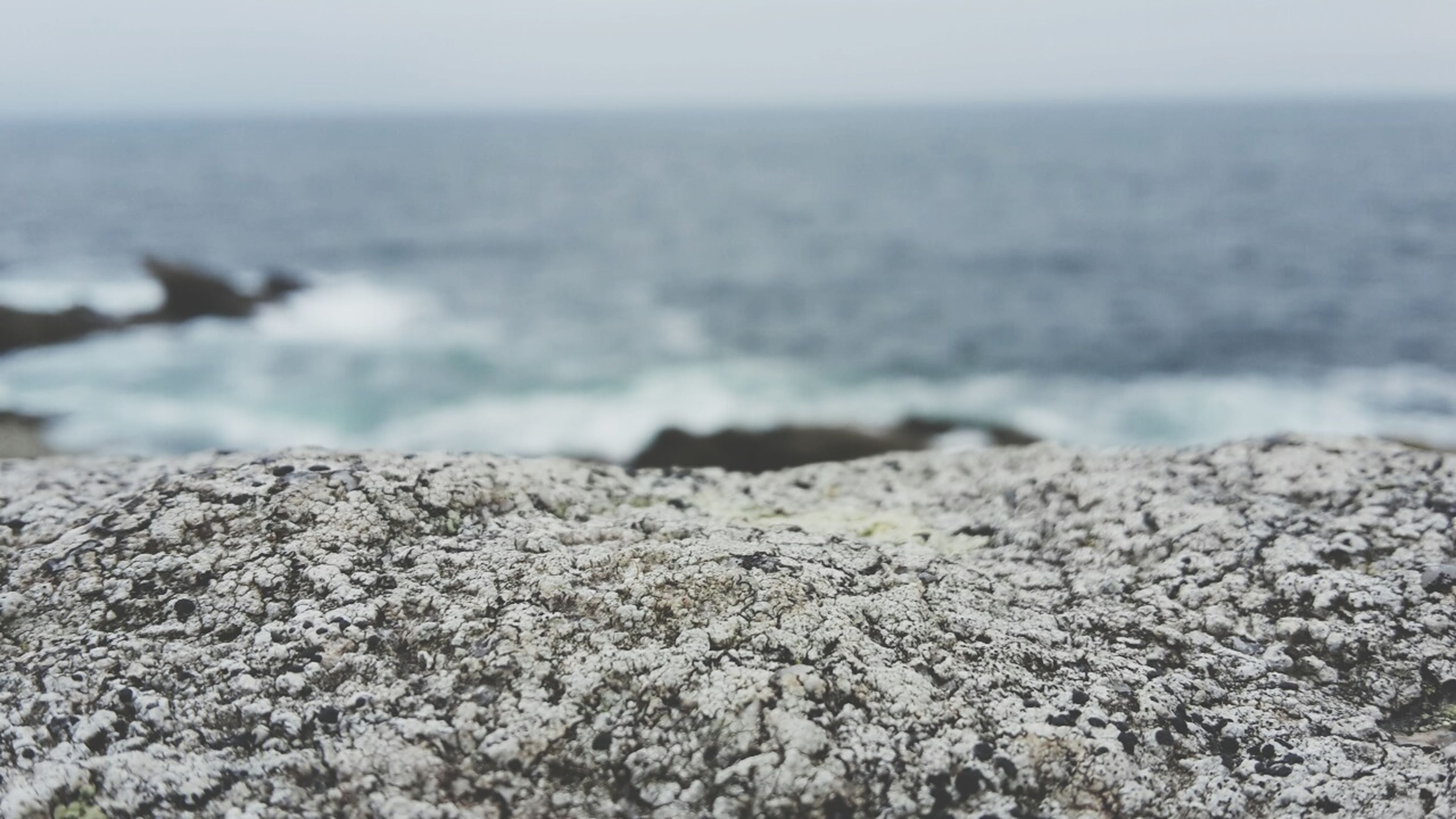 sea, beach, water, shore, horizon over water, tranquility, nature, tranquil scene, pebble, beauty in nature, scenics, focus on foreground, rock - object, sand, selective focus, surface level, stone - object, day, close-up, wave