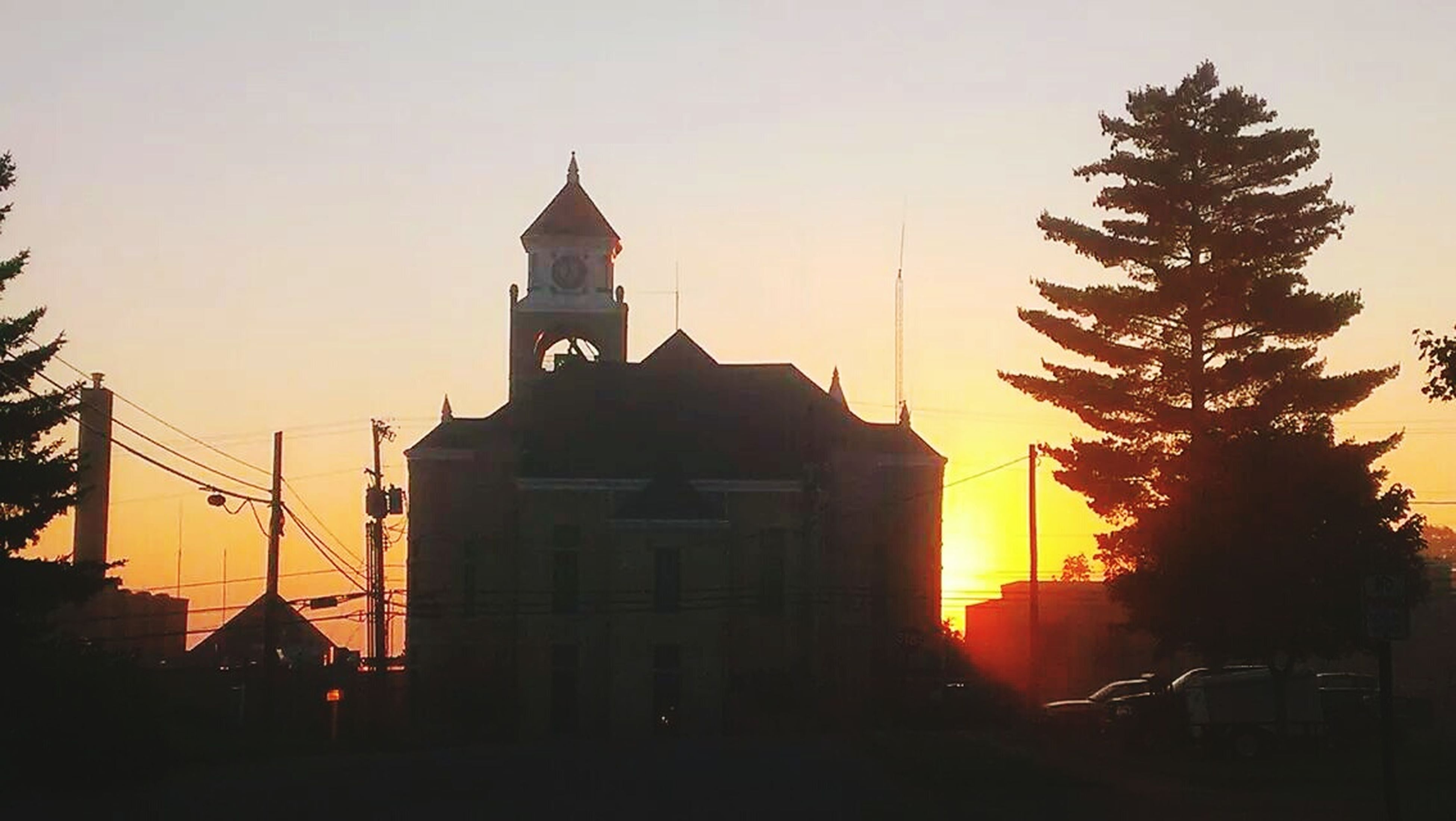 building exterior, architecture, sunset, built structure, place of worship, religion, spirituality, church, silhouette, clear sky, orange color, low angle view, sun, sky, copy space, tree, steeple, outdoors