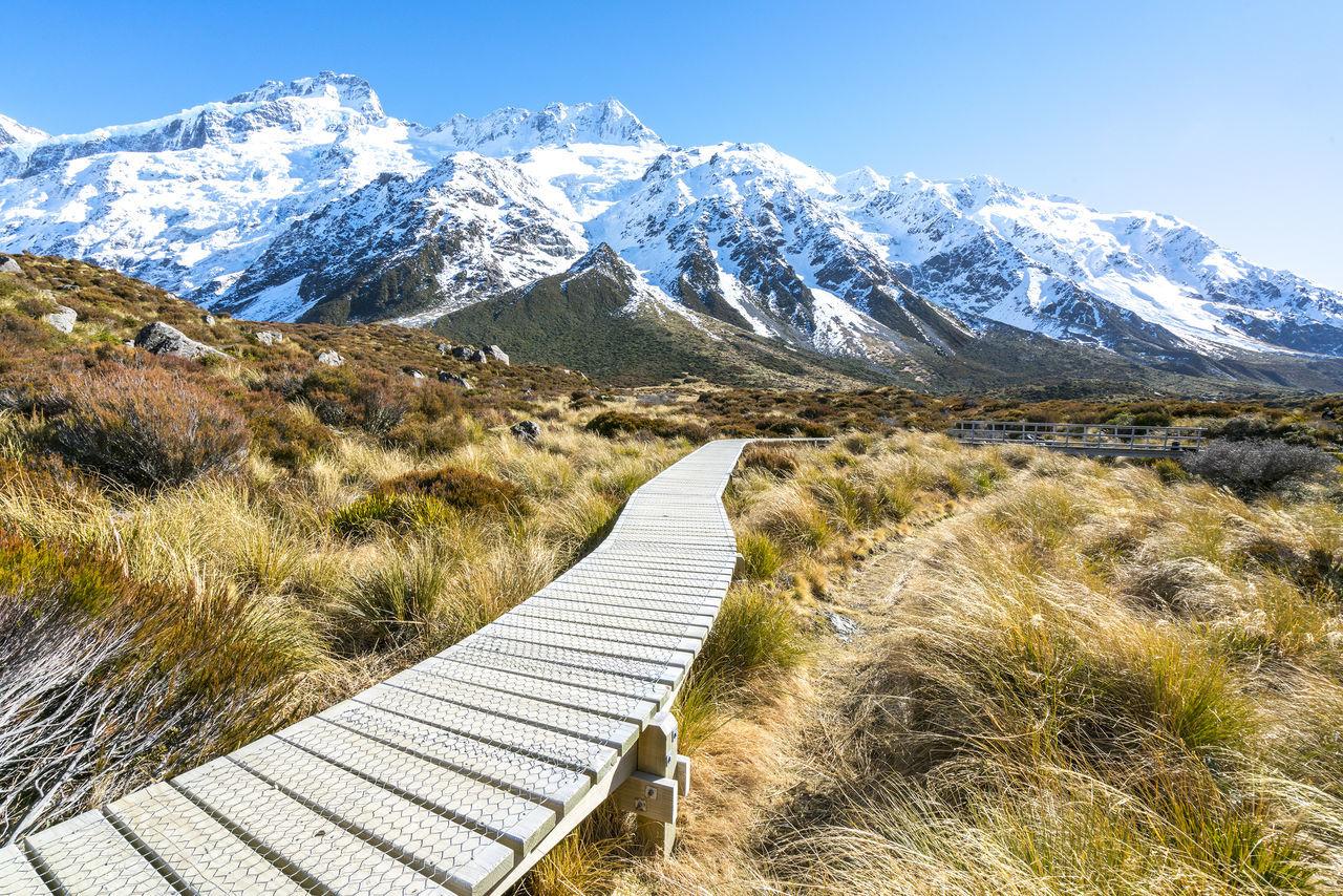 Narrow Boardwalk Leading Towards Snowcapped Mountains