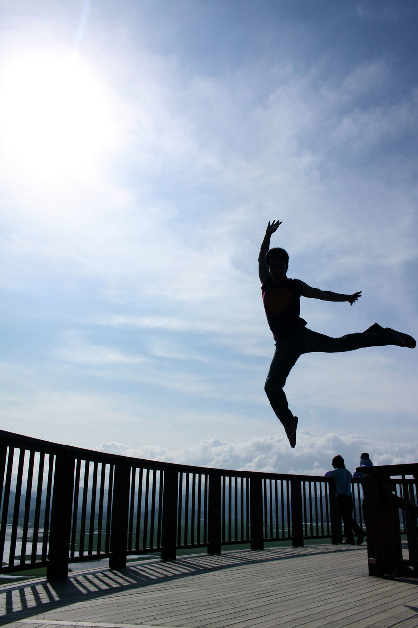 railing, sky, jumping, full length, mid-air, energetic, cloud - sky, day, outdoors, men, one person, leisure activity, real people, lifestyles, stunt, nature, people