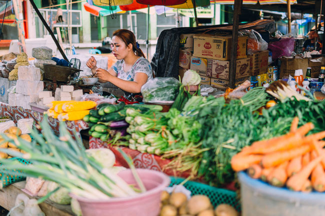Freshness Market Retail  Leisure Activity Casual Clothing Person Retail Display Arrangement Young Adult Selective Focus Market Stall Full Length Colorful Outdoors People Street Photography Large Group Of Objects Vegetable Vegetables & Fruits Vegetable Market Human Interest