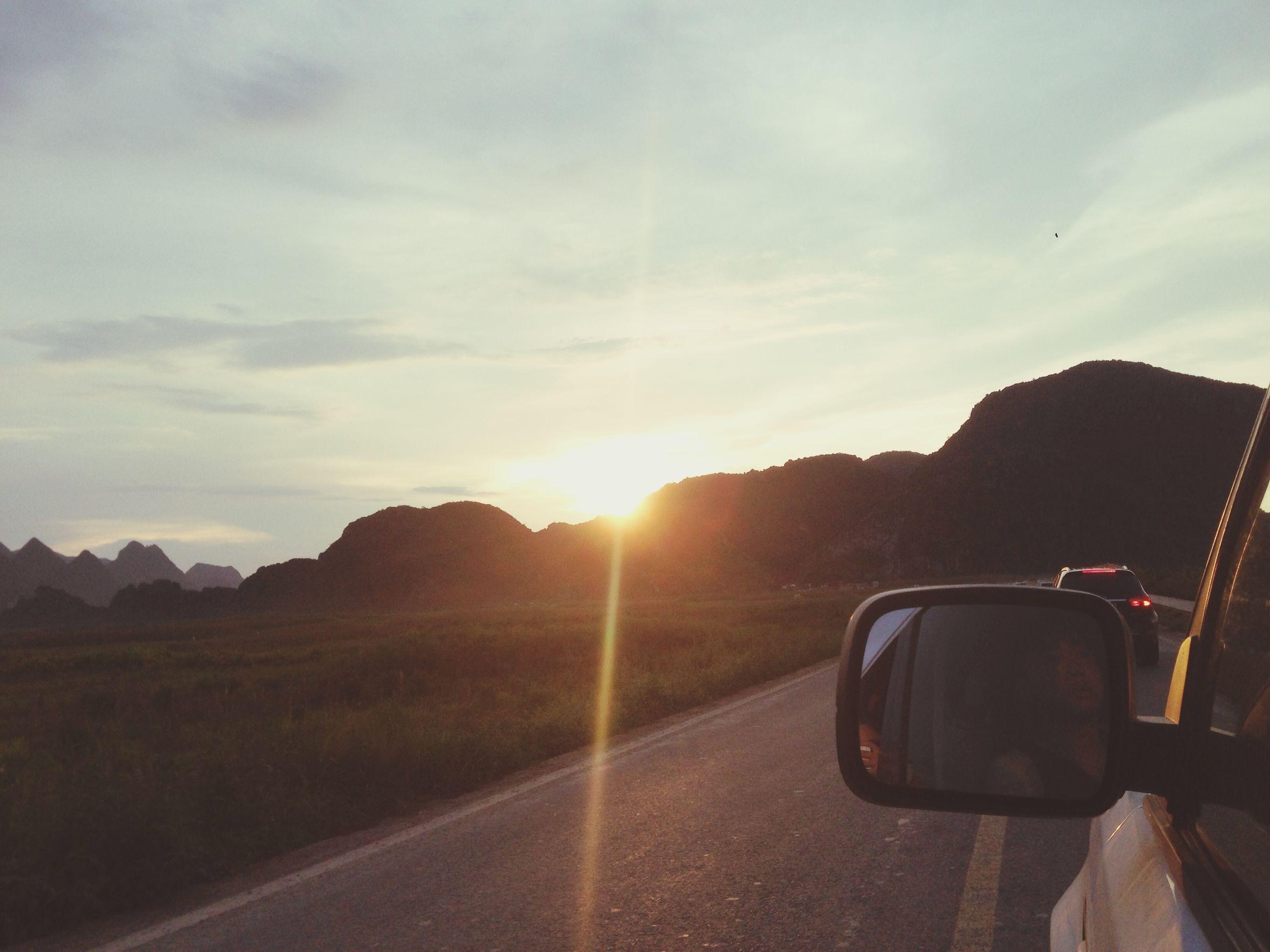 transportation, mountain, land vehicle, mode of transport, car, sun, sky, road, sunset, sunlight, mountain range, sunbeam, scenics, tranquil scene, beauty in nature, lens flare, landscape, tranquility, nature, cloud - sky