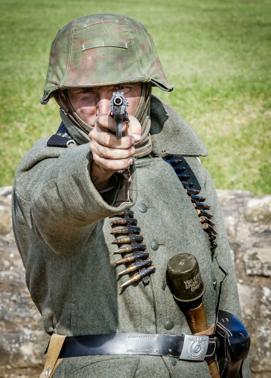 weapon, rifle, army, men, gun, military uniform, shooting a weapon, military, outdoors, camouflage clothing, holding, one person, army soldier, army helmet, headwear, one man only, adult, day, young adult, people, human hand, only men, adults only