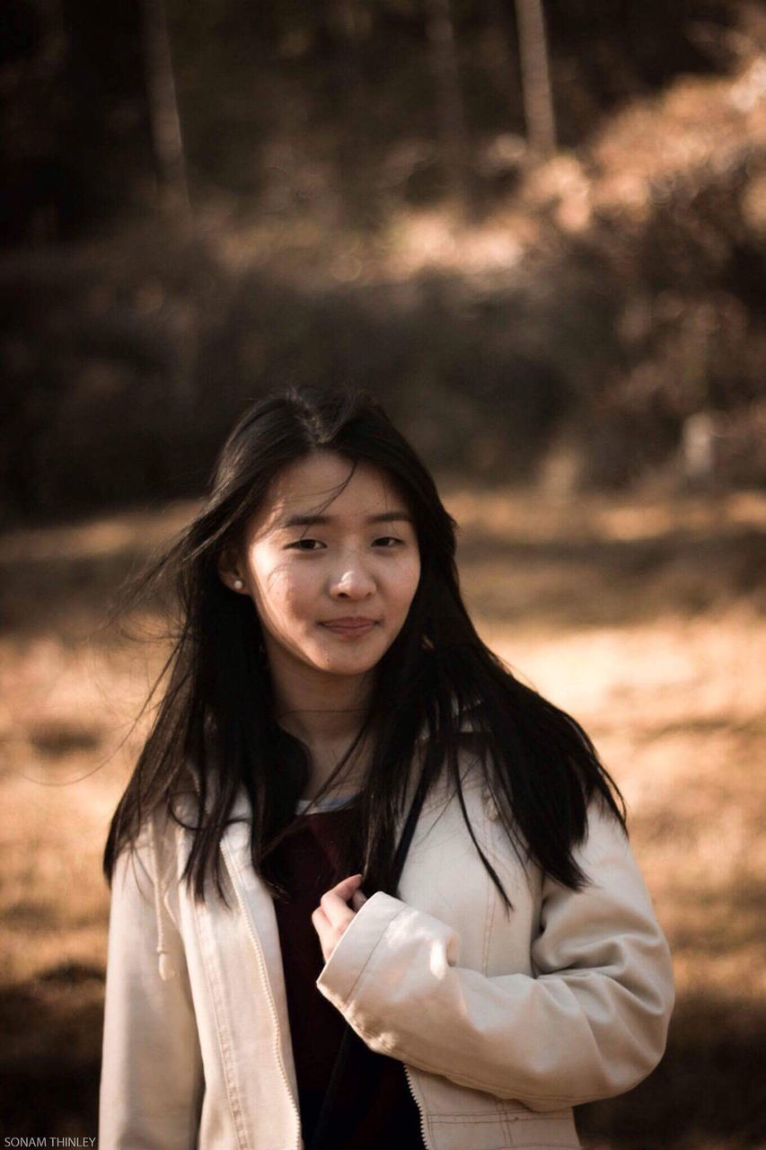 one person, front view, real people, looking at camera, long hair, black hair, casual clothing, leisure activity, young adult, focus on foreground, lifestyles, holding, portrait, standing, tree, beautiful woman, young women, medium-length hair, outdoors, smiling, day, nature, adult, people