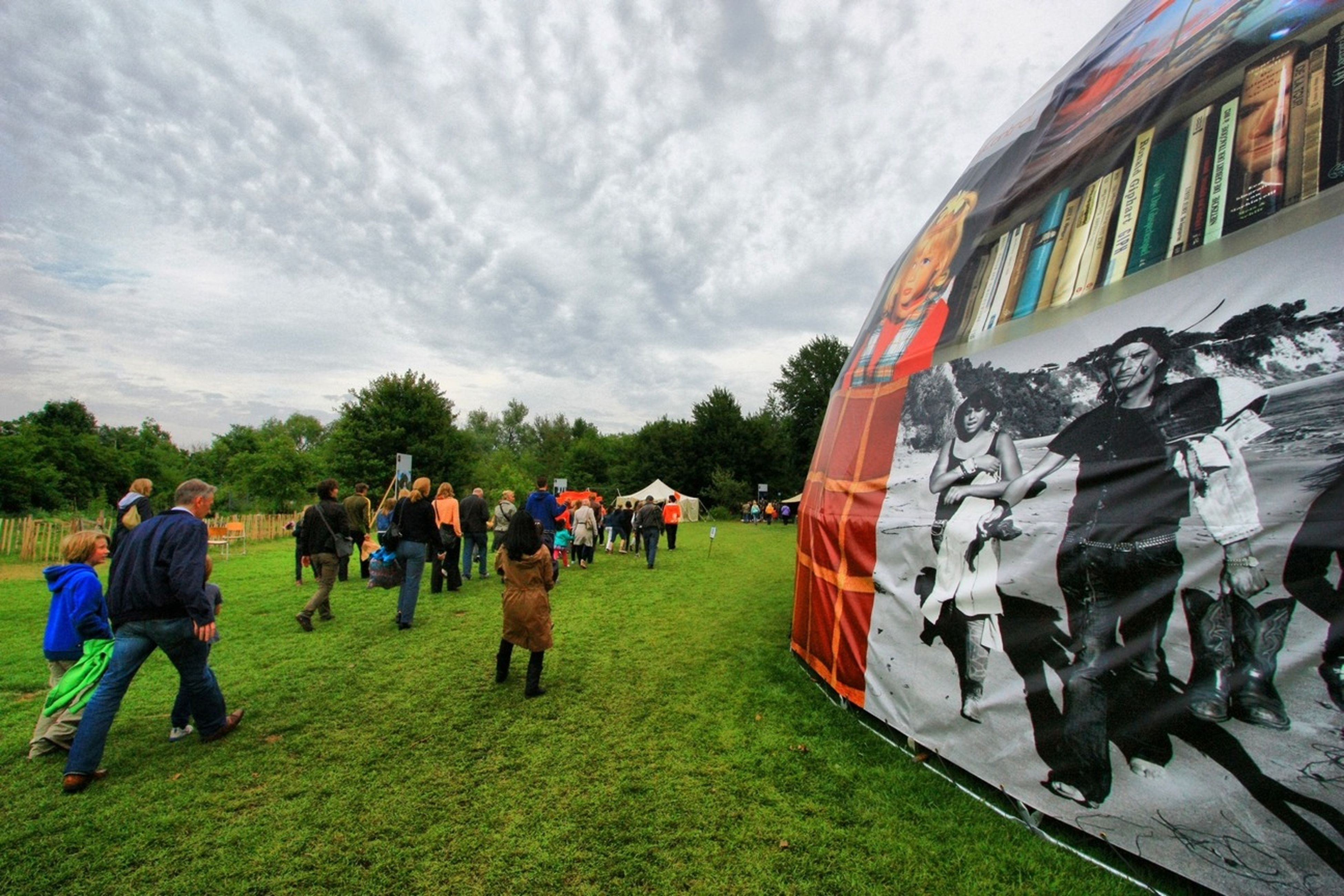 sky, cloud - sky, large group of people, grass, architecture, men, built structure, building exterior, cloudy, cloud, day, person, flag, field, outdoors, leisure activity, lifestyles, graffiti, tradition