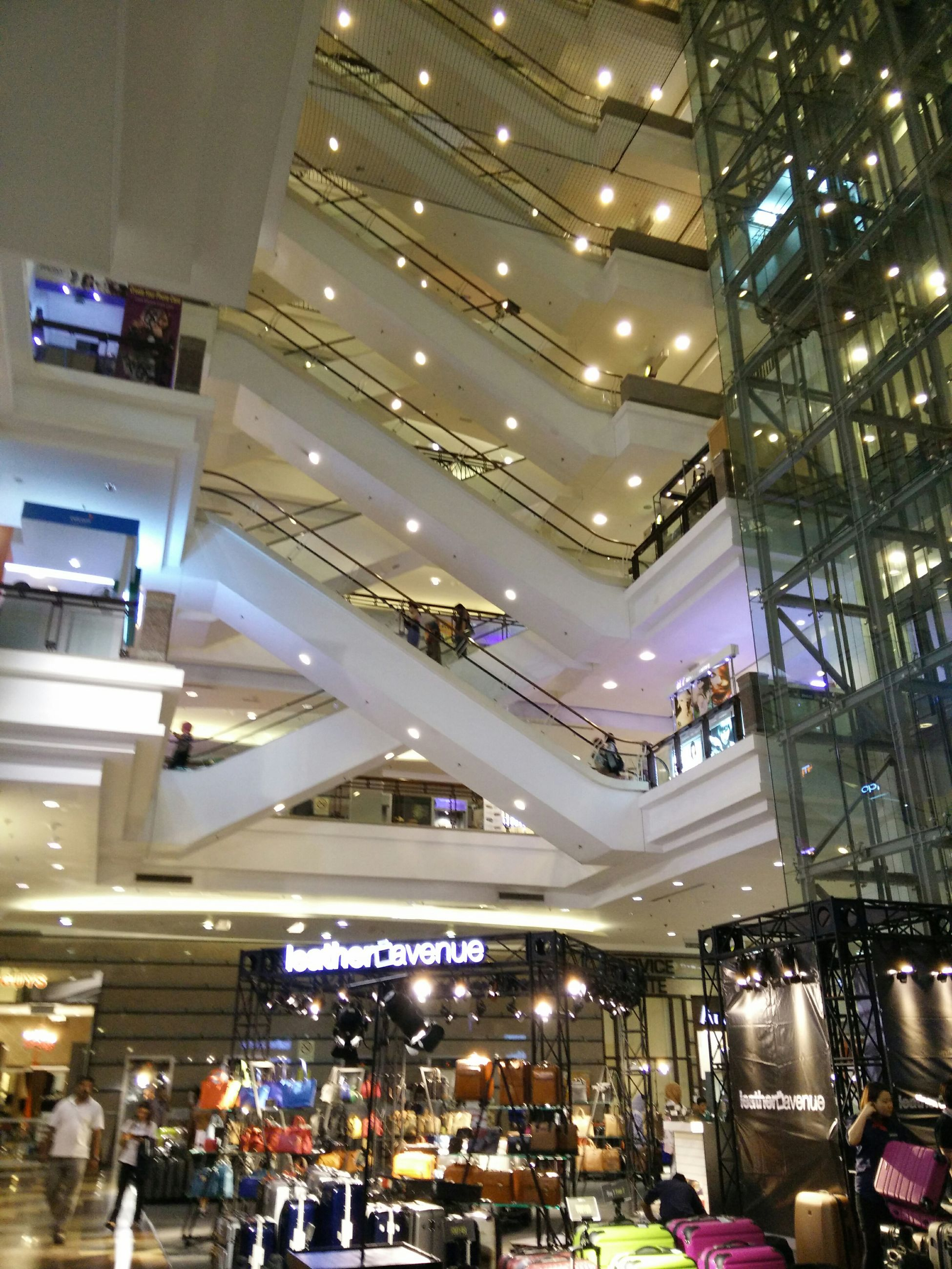 illuminated, indoors, lighting equipment, night, architecture, built structure, ceiling, incidental people, in a row, low angle view, modern, shopping mall, store, hanging, city, large group of objects, abundance, building exterior, city life, retail