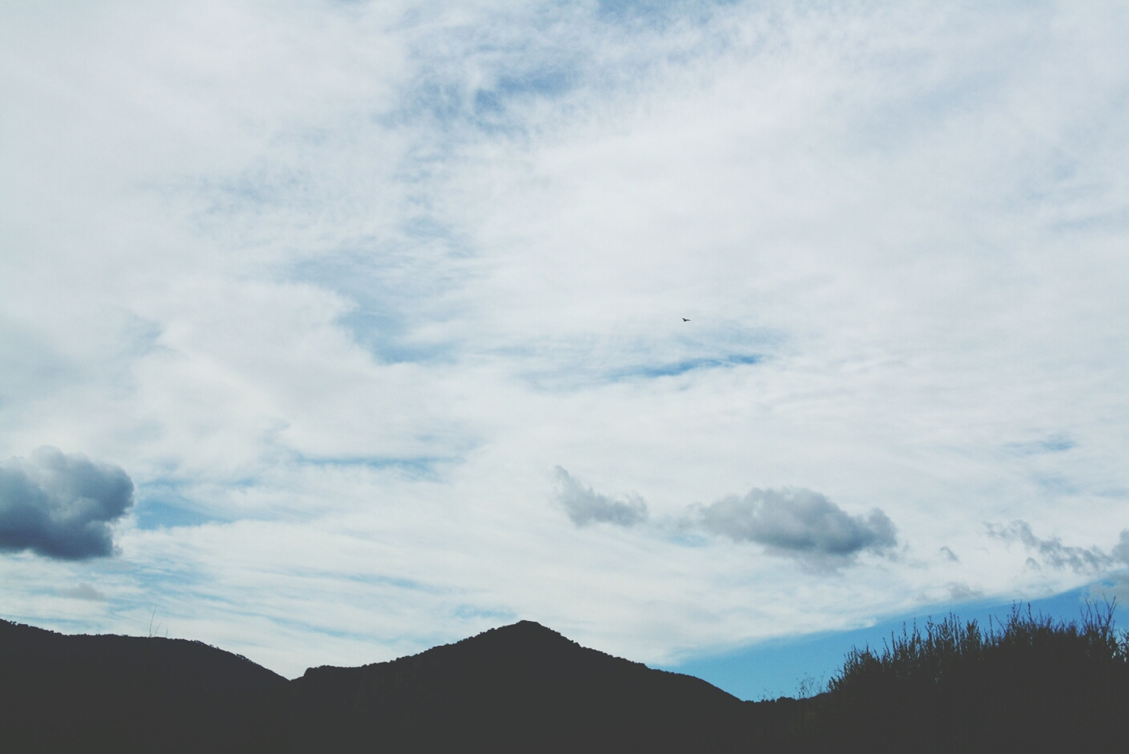 mountain, sky, tranquil scene, tranquility, scenics, beauty in nature, mountain range, cloud - sky, nature, low angle view, silhouette, cloud, cloudy, landscape, idyllic, tree, outdoors, non-urban scene, day, no people