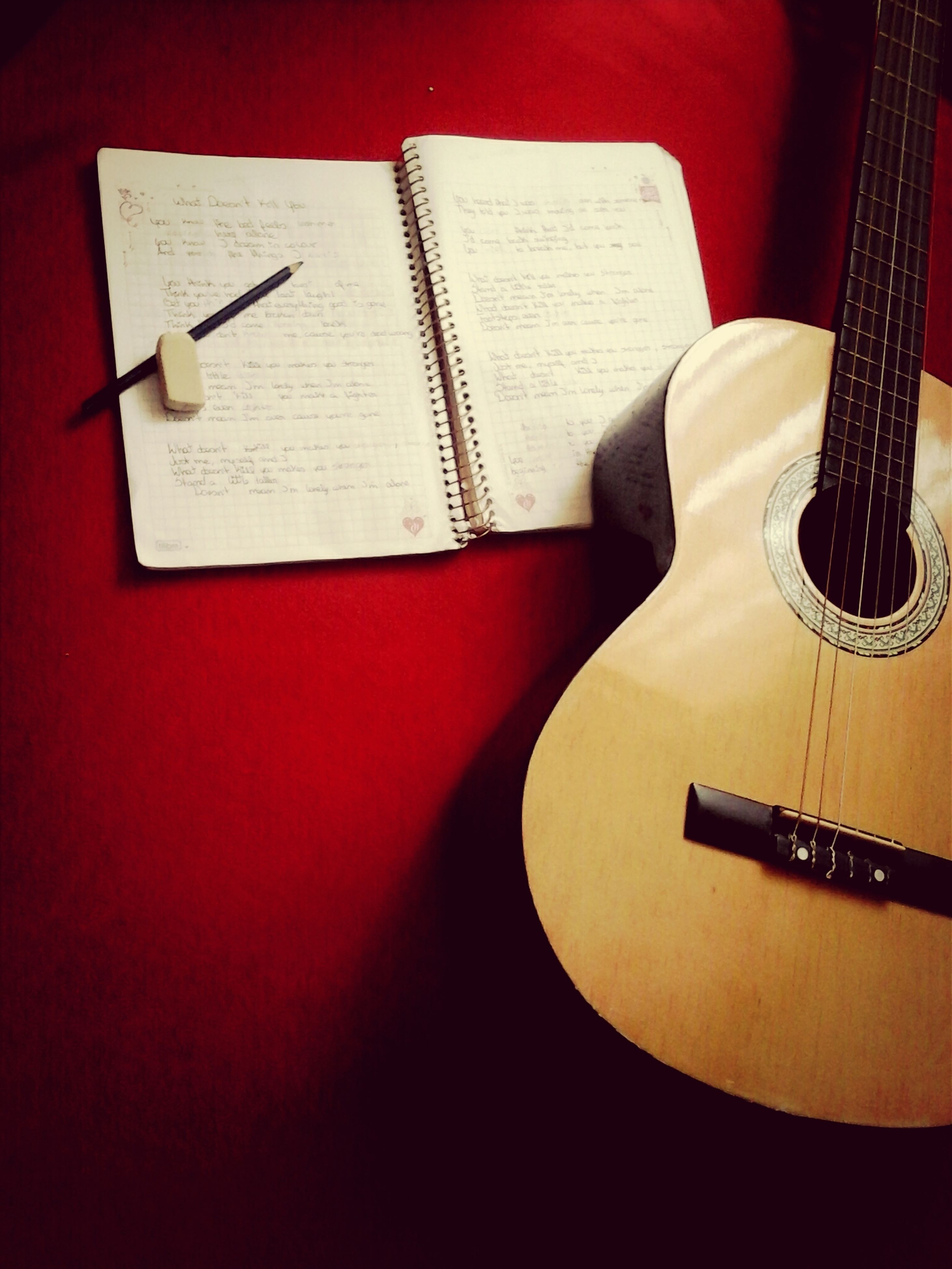 indoors, still life, table, music, close-up, high angle view, pen, book, musical instrument, paper, education, pencil, studio shot, page, single object, arts culture and entertainment, no people, guitar, musical equipment, technology