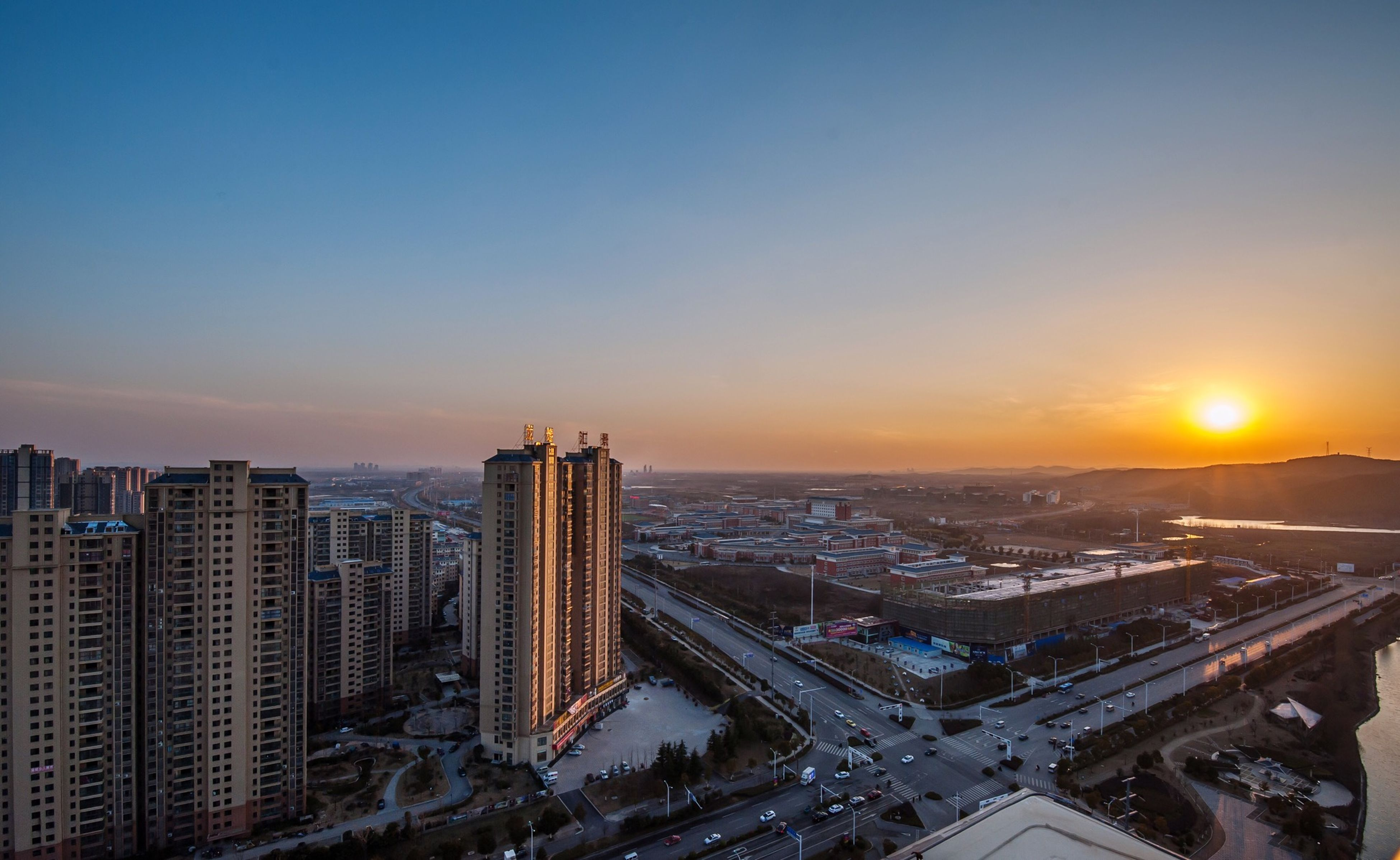 sunset, building exterior, city, architecture, cityscape, built structure, orange color, high angle view, copy space, clear sky, city life, illuminated, sky, crowded, residential building, residential district, no people, outdoors, skyscraper, aerial view
