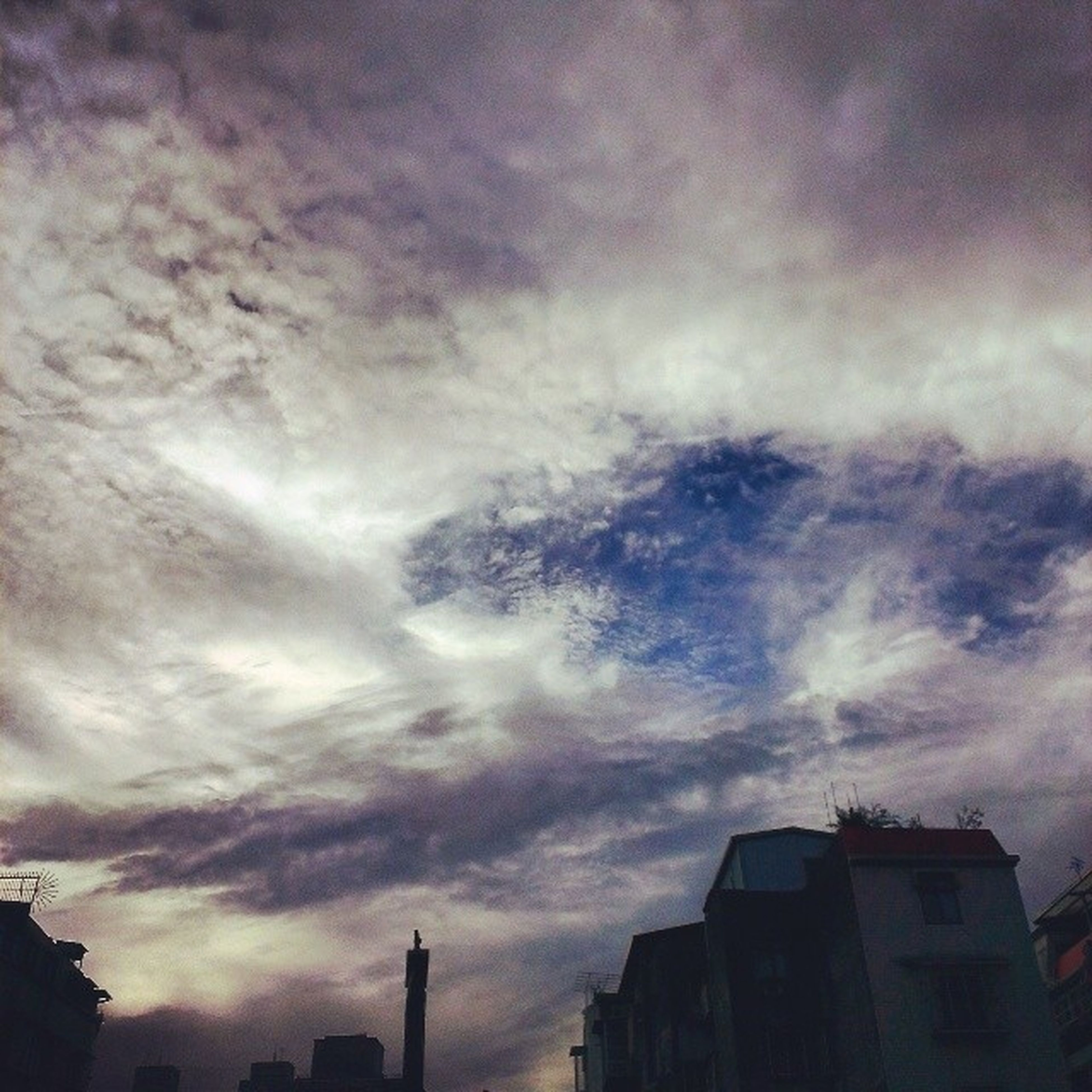 building exterior, architecture, built structure, sky, cloud - sky, cloudy, low angle view, silhouette, weather, overcast, building, cloud, storm cloud, city, dusk, sunset, residential structure, residential building, outdoors, dramatic sky