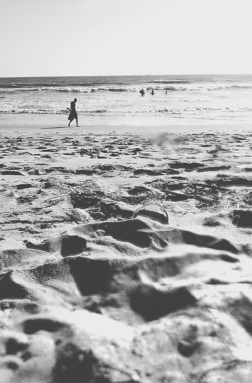 sea, beach, water, sand, shore, wave, one person, real people, horizon over water, nature, outdoors, full length, motion, silhouette, leisure activity, day, beauty in nature, vacations, scenics, men, ankle deep in water, sky, people