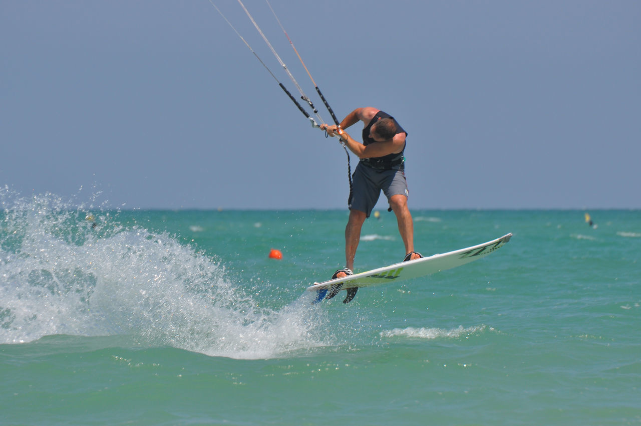 Kitesurfer wave Adult Adventure Challenge Clear Sky Control Day Extreme Sports Full Length Kiteboarding Kitesurfer Low Angle View Men Motion Nature One Person Only Men Outdoors People Sea Skill  Sport Vacations Wave Young Adult