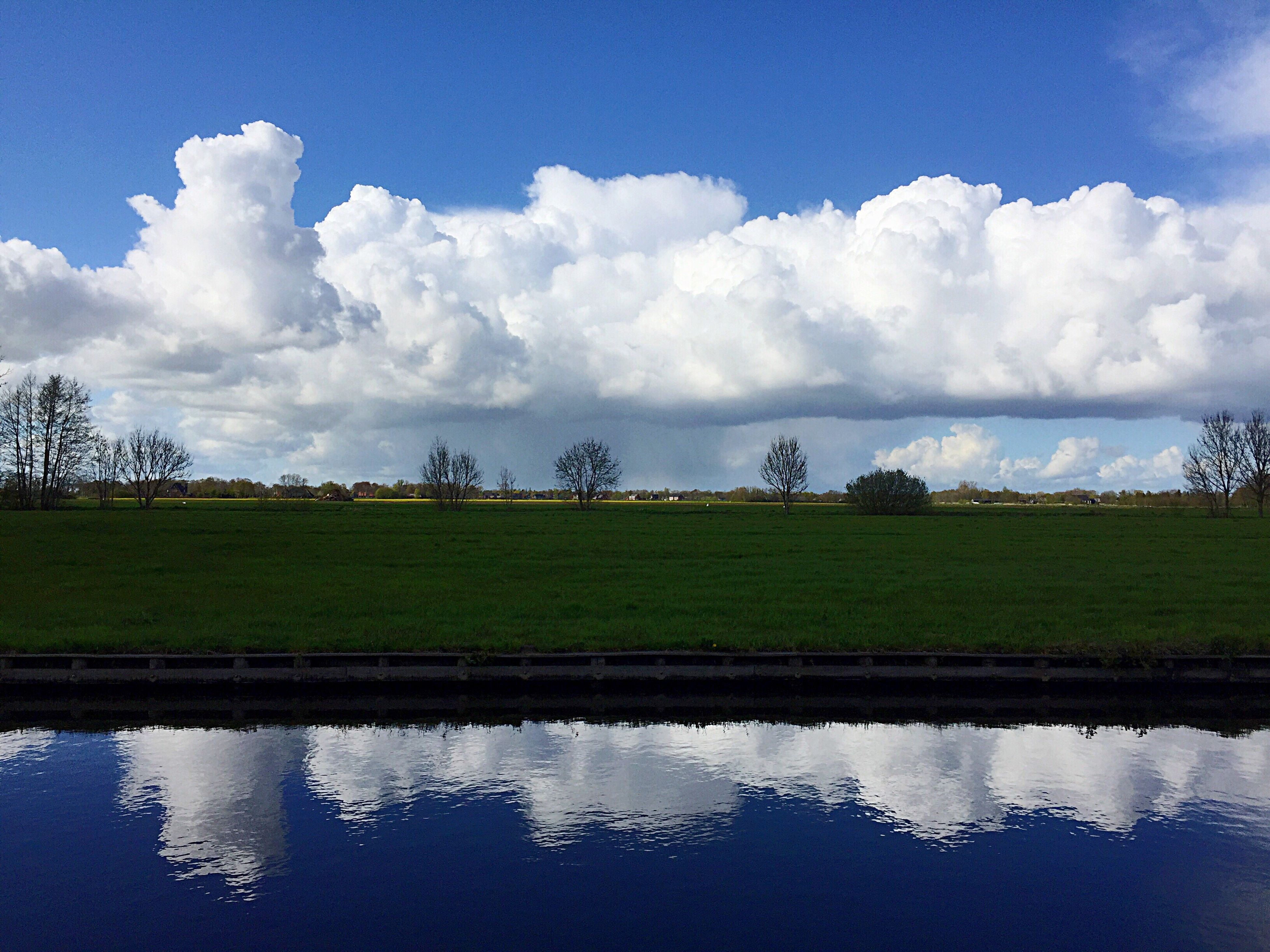 sky, water, tranquil scene, tranquility, field, rural scene, grass, agriculture, landscape, scenics, nature, beauty in nature, green color, reflection, growth, cloud - sky, farm, cloud, lake, waterfront