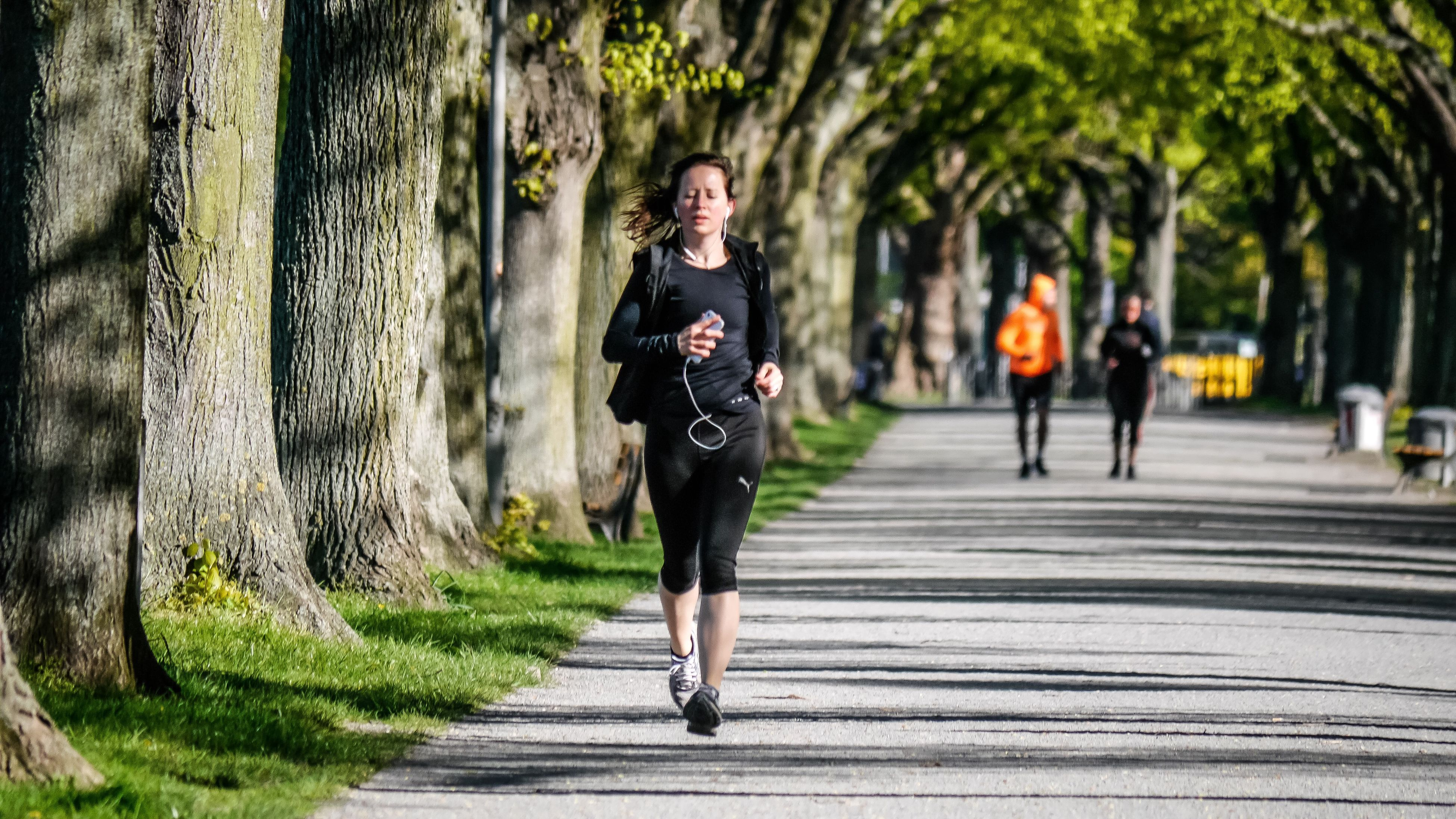 jogging, running, full length, exercising, lifestyles, sports clothing, outdoors, real people, sport, day, women, healthy lifestyle, leisure activity, one person, young women, only women, tree, adults only, young adult, people, adult, blond hair, marathon, athlete, nature