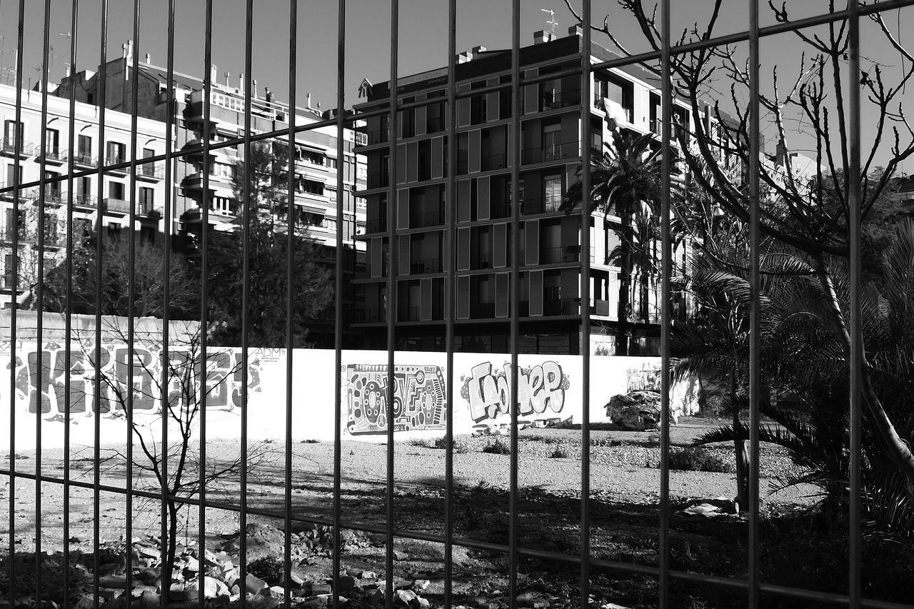 Graffiti On Wall Seen Through Railing