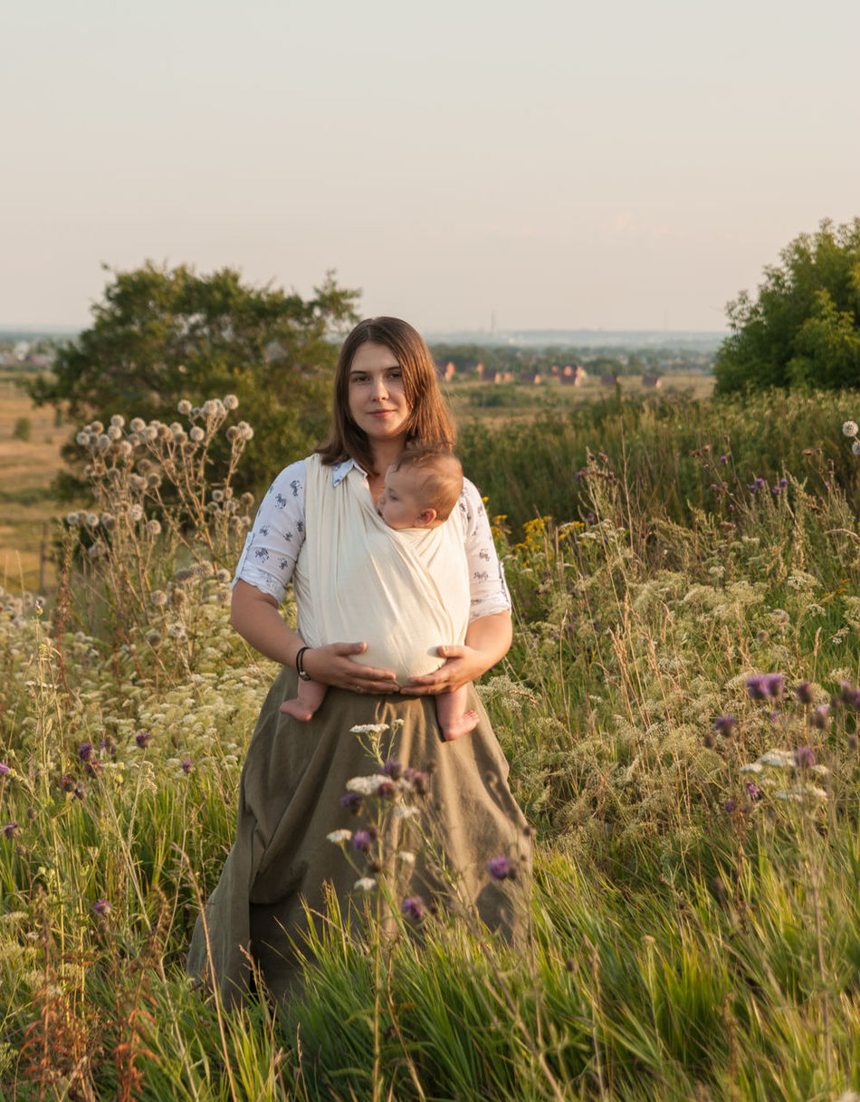 Come, step with me into grasslands Baby Baby Sling Baby Wrap Babywearing Bonding Carefree Childhood Children Family Field Golden Hour Grass Lifestyle Looking At Camera Love Maternity Mom Mother And Son Motherhood Outdoors Parenting Rural Scene Sling Summer Woman