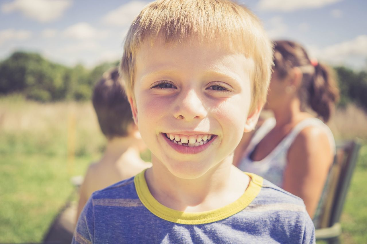 Portrait Looking At Camera Child Smiling Happiness Cheerful Joy Fun Children Only Childhood Headshot Anthropomorphic Smiley Face Carefree Enjoyment Outdoors Summer One Person Blond Hair Confidence  Grass