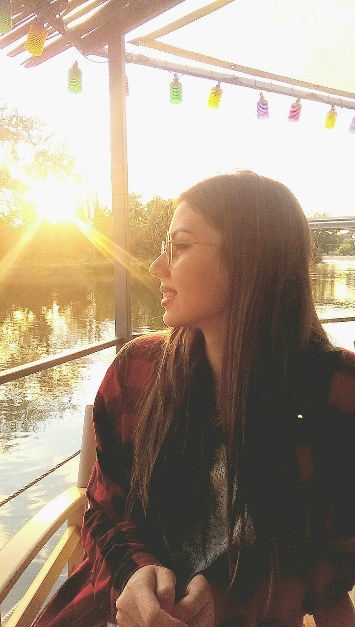 Beautiful Woman Sitting By Railing During Sunset