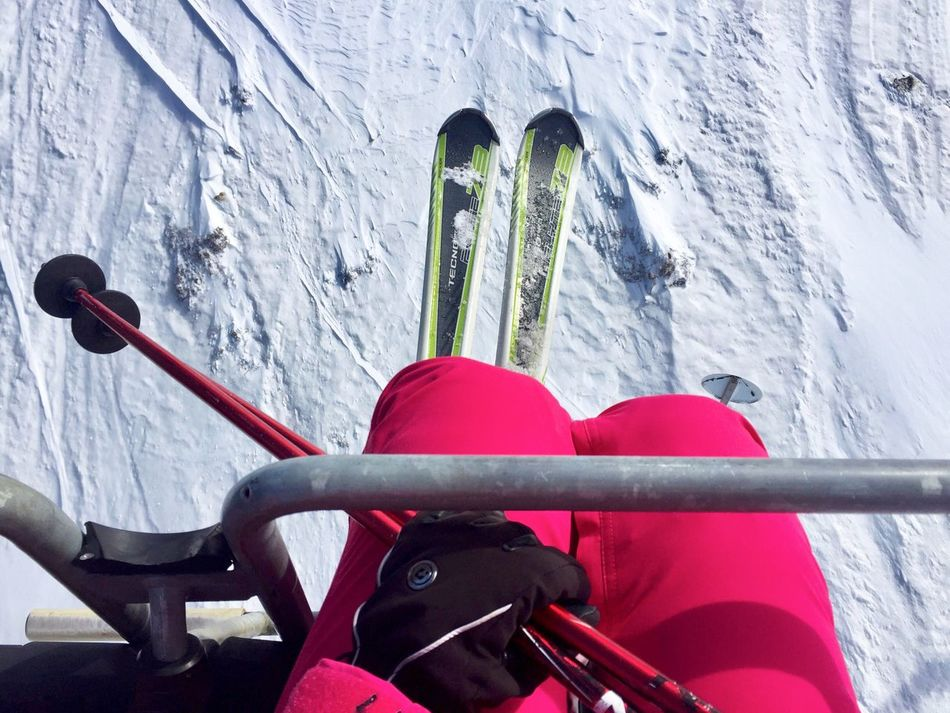 View from above of woman skier in the teleski wearing gloves and holding ski poles Red Lifestyles Mode Of Transport Leisure Activity Outdoors One Person Close-up Handlebar Teleski Skilift Slope Winter Snow Mountains Sports Air Transport Skier Feet Legs Skipoles Hand Hold Woman