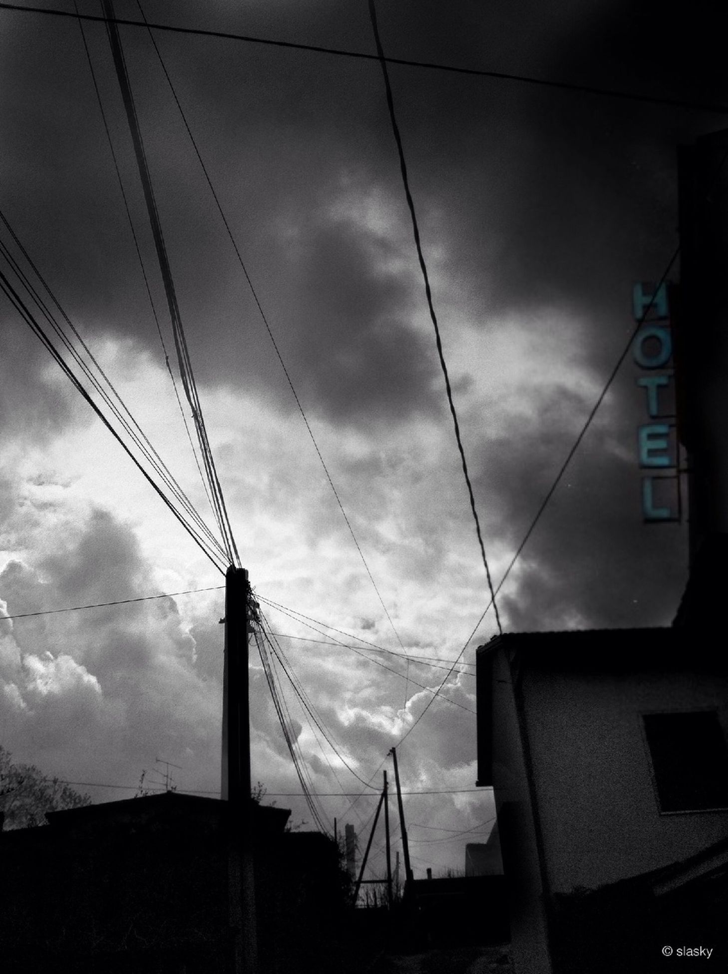 sky, building exterior, power line, architecture, built structure, cloud - sky, low angle view, cable, electricity, electricity pylon, cloudy, power supply, cloud, communication, connection, technology, no people, outdoors, fuel and power generation, day