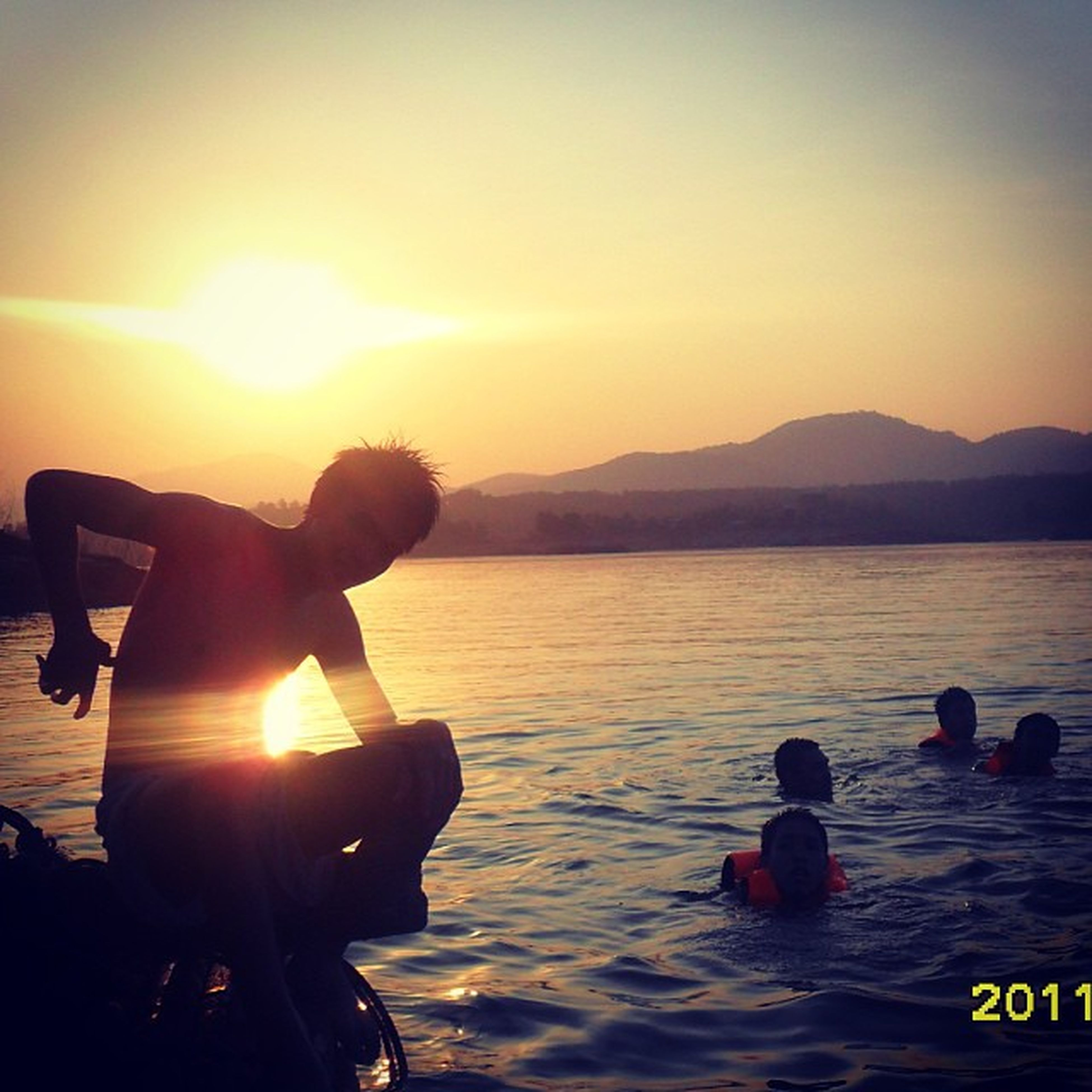sunset, water, sun, lifestyles, leisure activity, sea, silhouette, beach, men, orange color, scenics, sunlight, sky, togetherness, vacations, beauty in nature, reflection, mountain