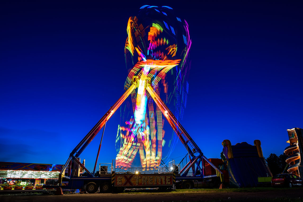 Attraction Amusement Park Amusement Park Ride Architecture Arts Culture And Entertainment Attraction Blue Clear Sky Ferris Wheel Illuminated Leisure Activity Long Exposure Multi Colored Night Night Photography Outdoors Sky