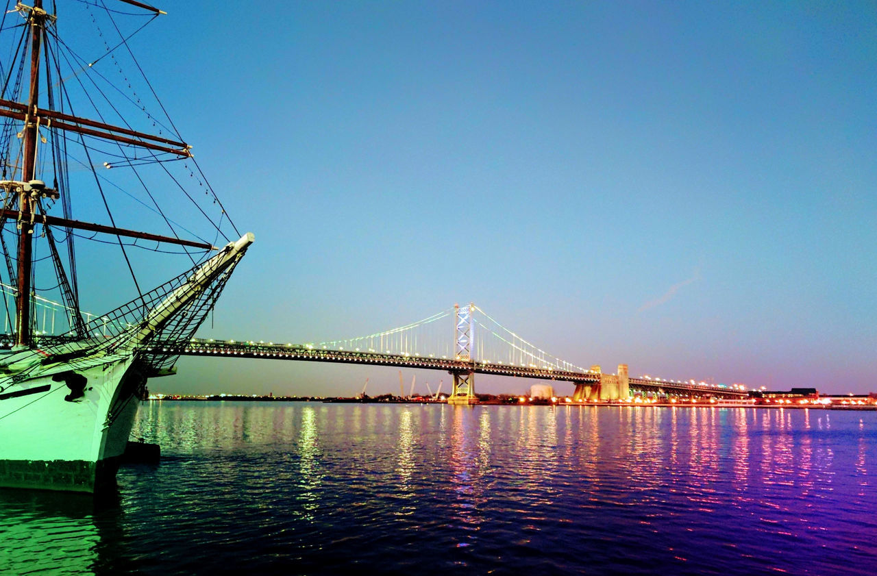 bridge - man made structure, connection, suspension bridge, transportation, engineering, architecture, built structure, travel destinations, clear sky, copy space, water, river, outdoors, waterfront, travel, sky, tourism, blue, no people, nautical vessel, bridge, day, low angle view, nature, city