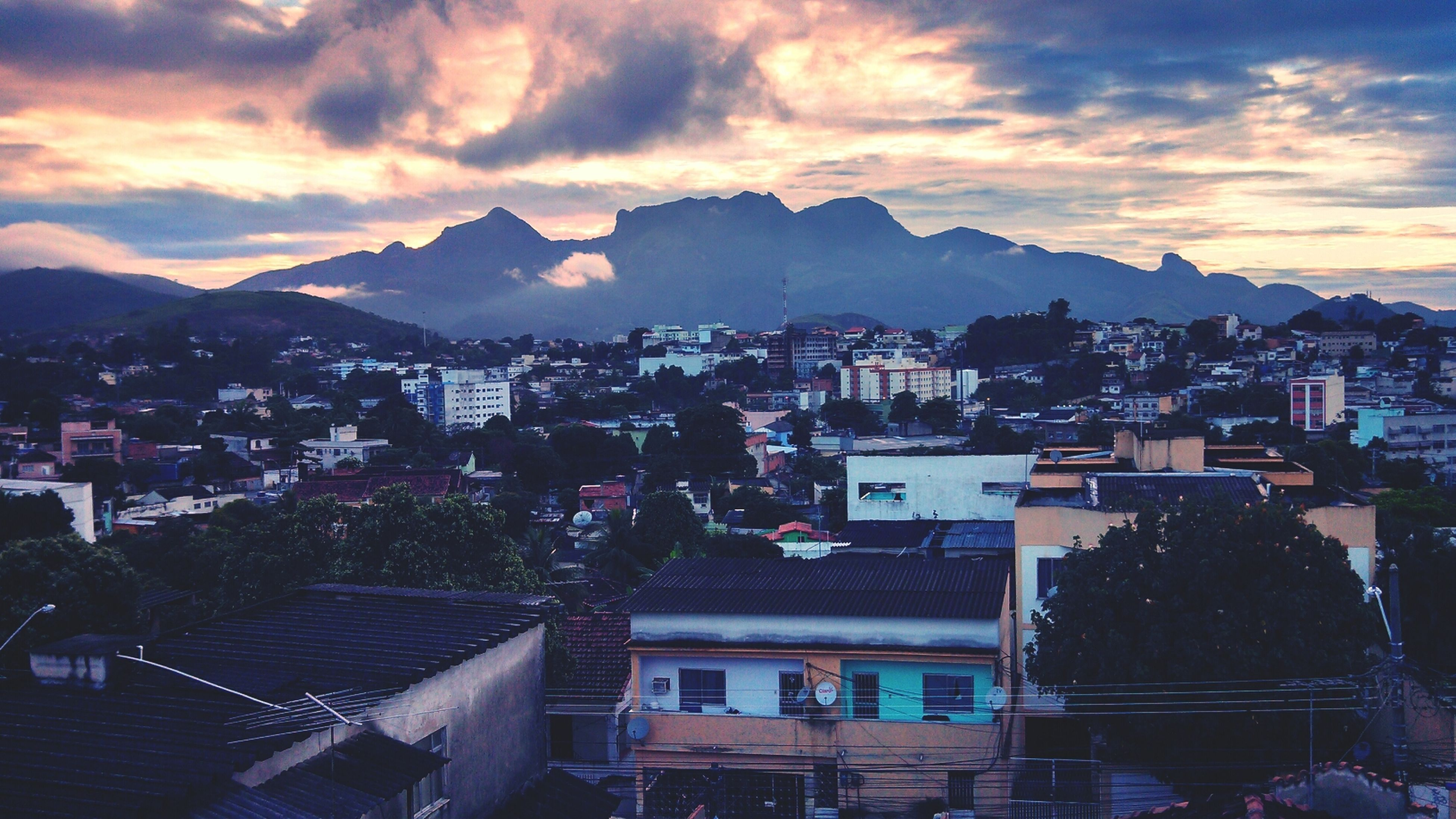 building exterior, architecture, built structure, mountain, cityscape, city, sunset, residential district, sky, residential building, residential structure, mountain range, crowded, high angle view, house, cloud - sky, town, townscape, community, cloud
