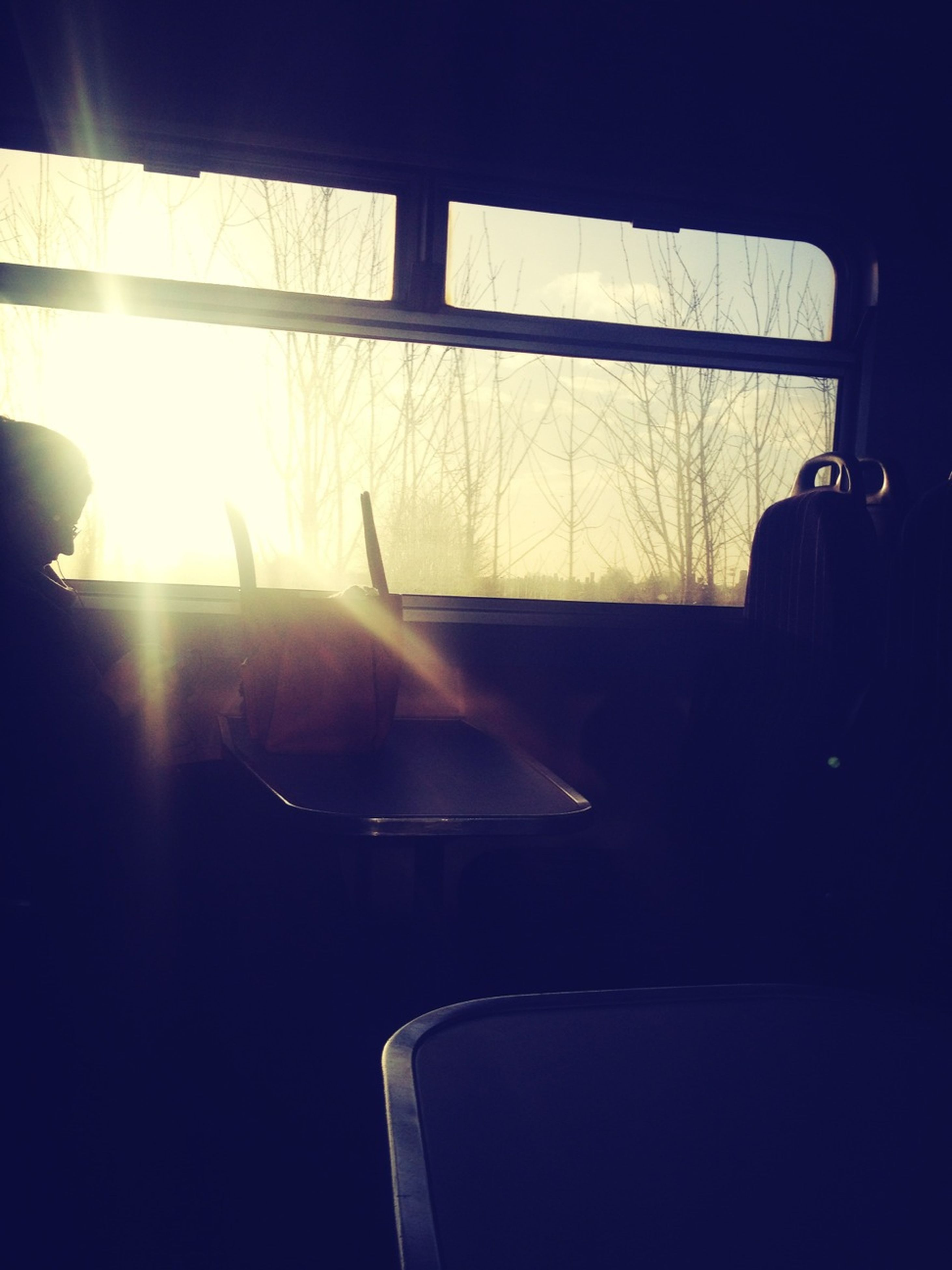 indoors, window, vehicle interior, sunlight, glass - material, silhouette, transparent, sun, sunbeam, transportation, sitting, mode of transport, lens flare, reflection, part of, chair, dark, cropped
