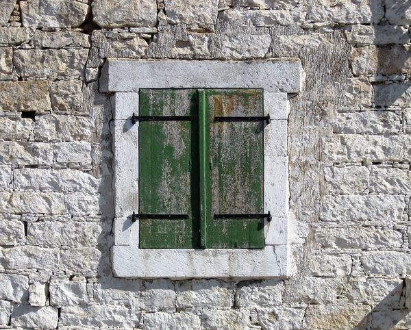 Green wooden closed window shutters with metal hinges set in a painted brick wall on a Cyprus village house. Architecture Brick Wall Background Brick Work Building Exterior Close-up Green Green Shutters Metal Hinge Window Wooden Window Shutters