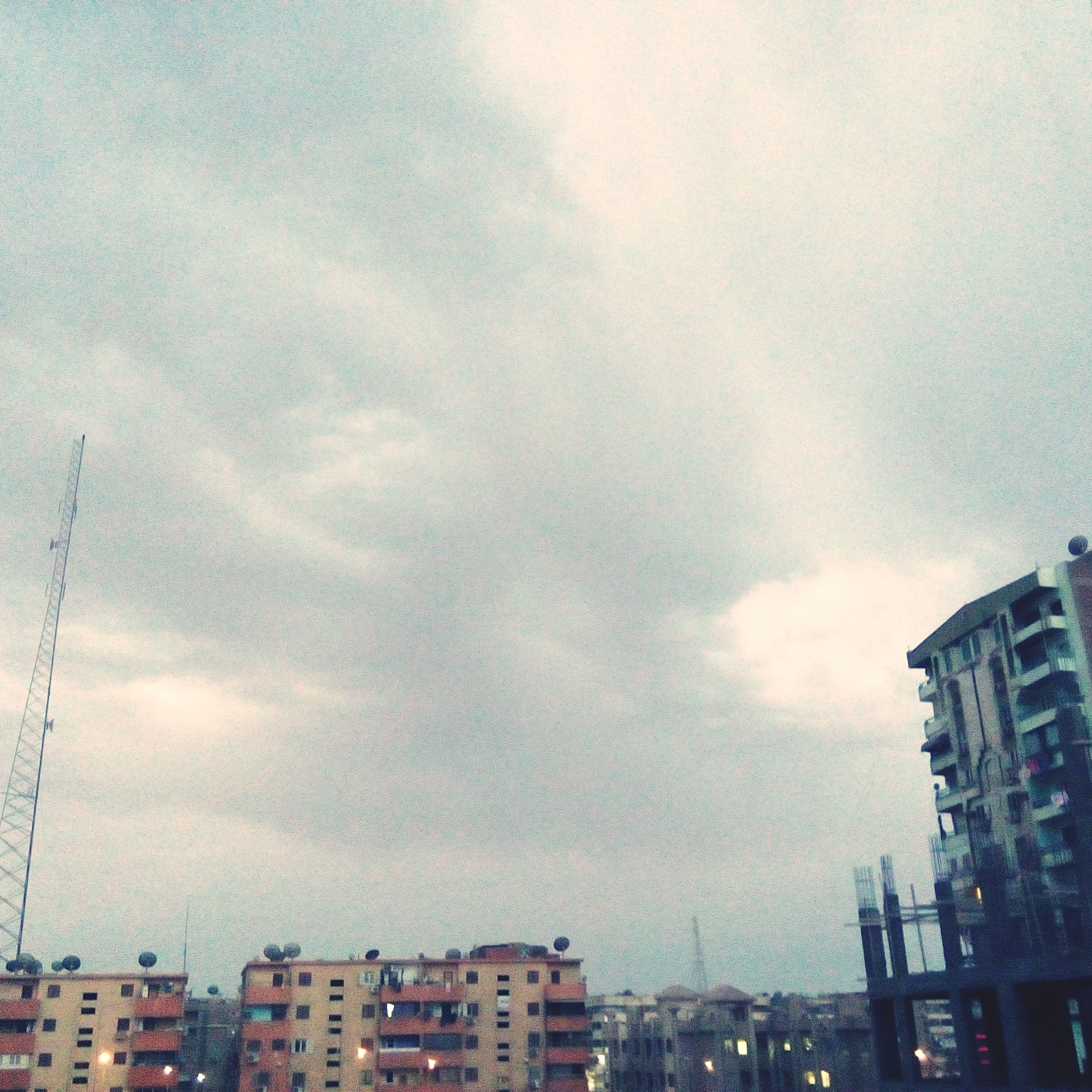 building exterior, architecture, built structure, sky, cloud - sky, city, low angle view, cloudy, residential building, residential structure, building, cloud, residential district, cityscape, weather, overcast, outdoors, no people, city life, dusk