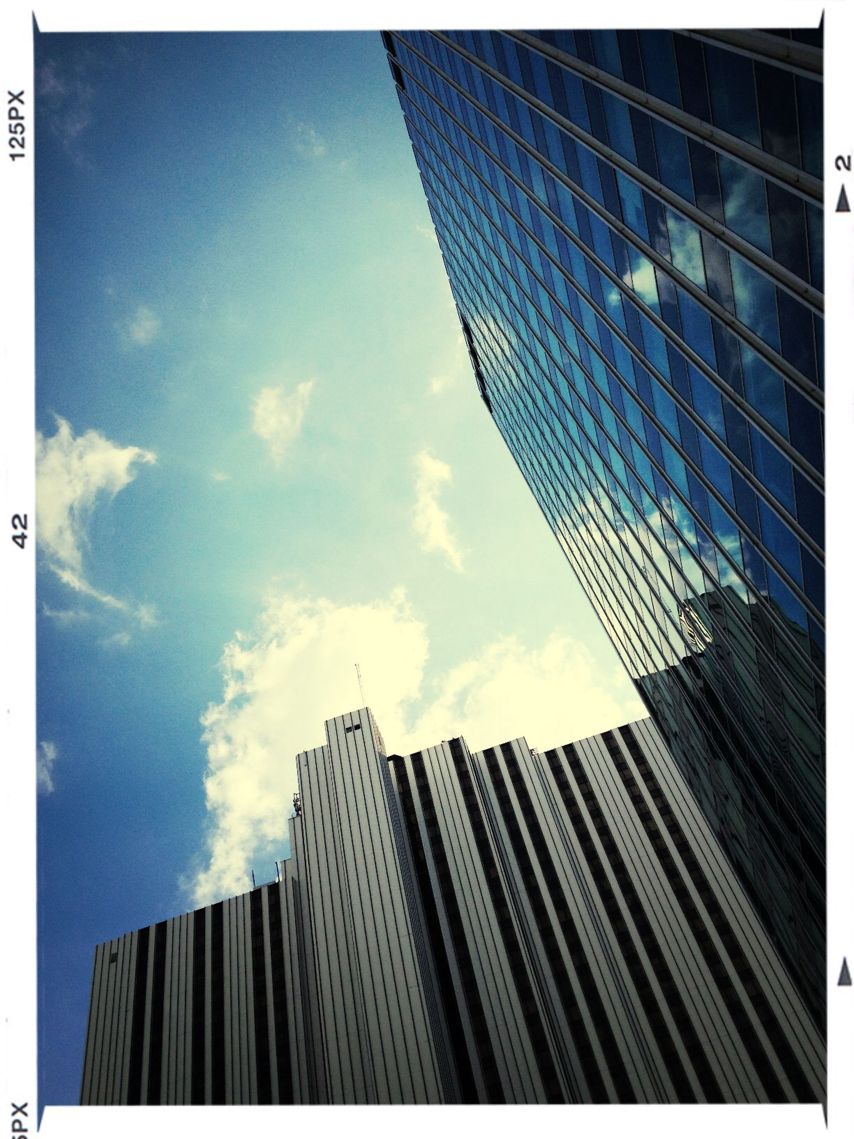 building exterior, architecture, built structure, low angle view, skyscraper, office building, transfer print, city, modern, tall - high, tower, sky, auto post production filter, building, tall, cloud - sky, day, cloud, outdoors, glass - material