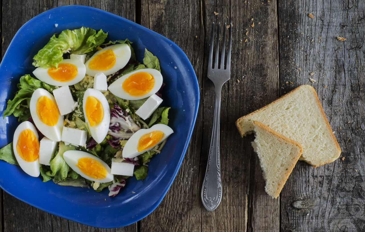 High angle view of green salad wth boiled eggs and feta cheese in blue bowl on a weathered old wooden table Blue Boiled Bowl Cheese Egg Yolk Eggs Feta Food Food And Drink Fork Freshness Green Healthy Eating High Angle View No People Old Ready-to-eat Salad Table Weathered Wood - Material Wooden