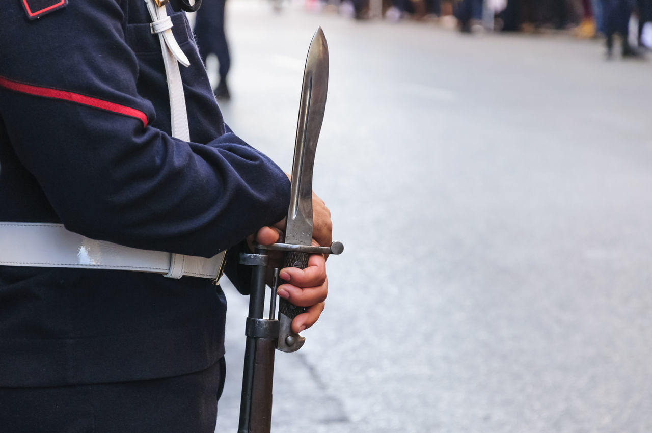 A close up of a Spanish sailor holding a rifle with a fixed bayonet in Madrid. Bayonet Cavalry Close-up Day Editorial  Empty Guard Hands Holding Human Body Part Human Hand Midsection Military Military Life News One Man Only One Person Outdoors People Rifle Standing Street Travel Uniform