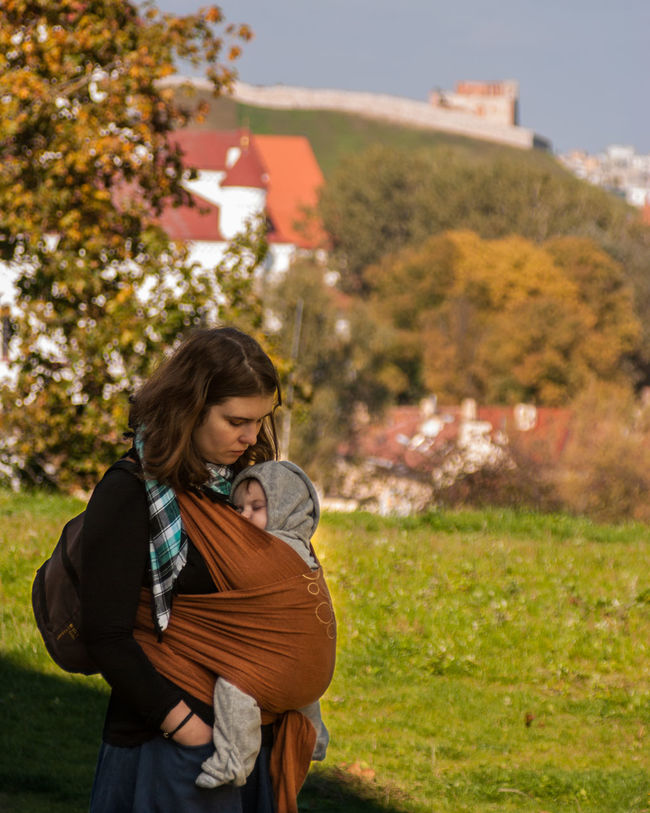 The Old City of Vilnius is near Autumn Baby Baby Sling Baby Wrap Babywearing Bonding Childhood Children Day Family Leisure Activity Lifestyle Love Maternity Mom Mother And Son Motherhood Outdoors Parenting Selective Focus Sling Standing Vilnius Waist Up Woman