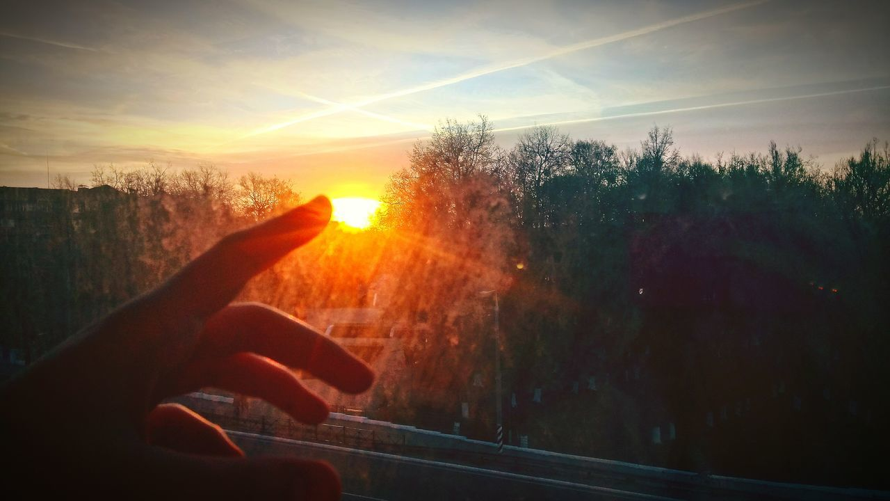 sunset, human hand, sun, sky, silhouette, one person, transportation, tree, nature, real people, human body part, sunlight, outdoors, beauty in nature, scenics, landscape, close-up, day, people