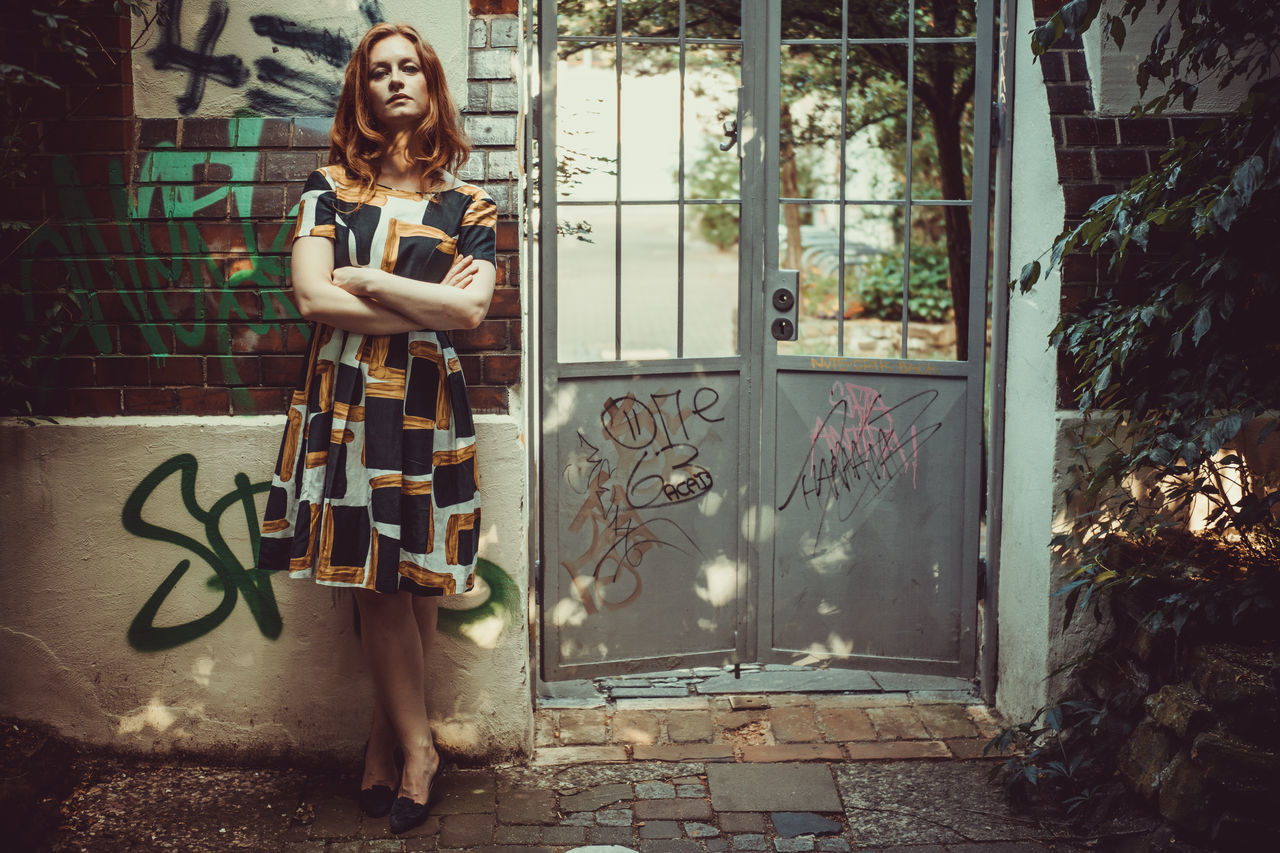 Young woman in a summer dress standing left to a closed gate Adult Day Full Length Graffiti Lifestyles One Person One Woman Only Outdoors People Portrait Real People Standing Young Adult