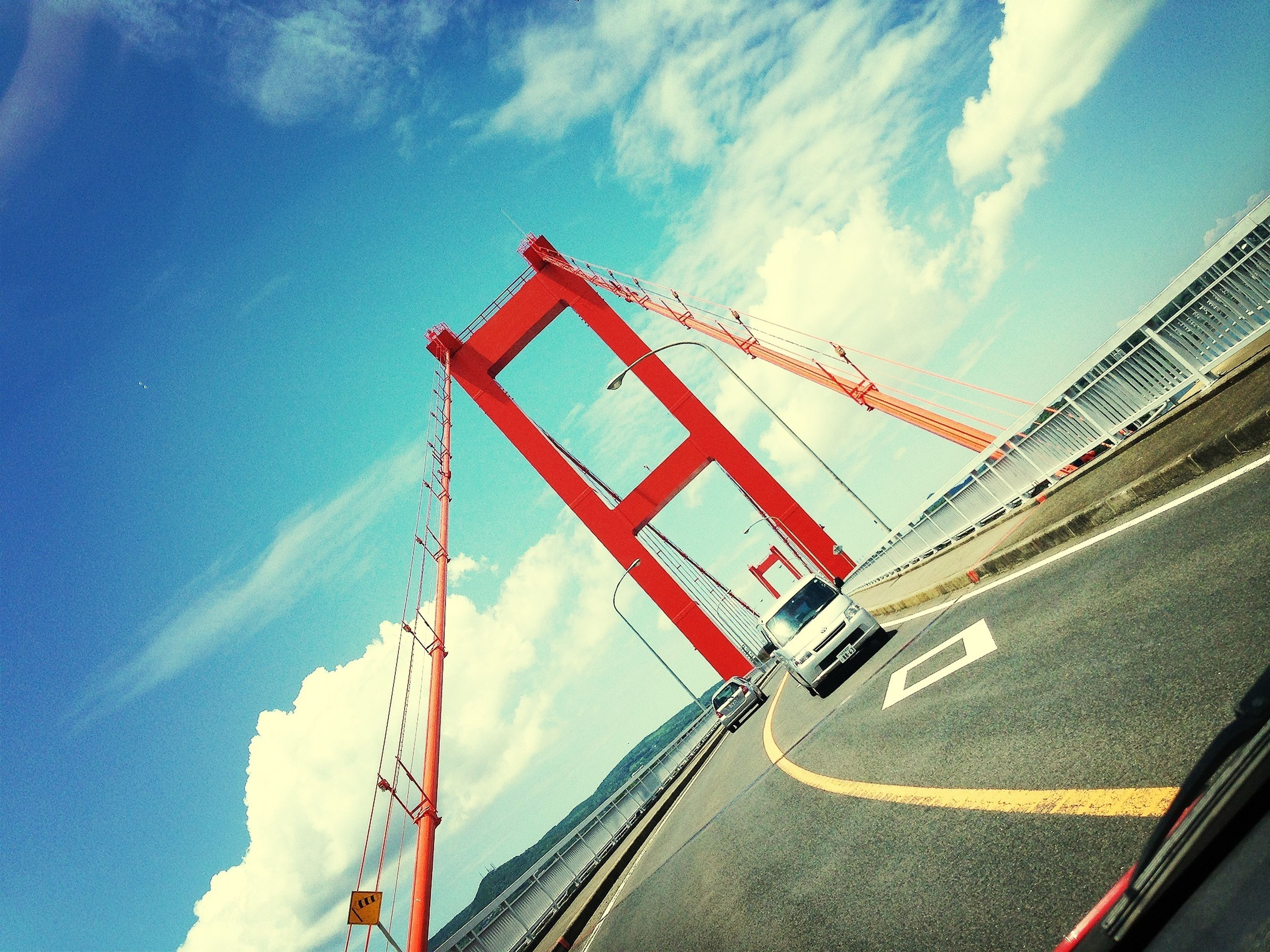 transportation, sky, red, built structure, architecture, cloud - sky, low angle view, mode of transport, bridge - man made structure, connection, day, cloud, outdoors, railing, flag, no people, travel, road, engineering, blue