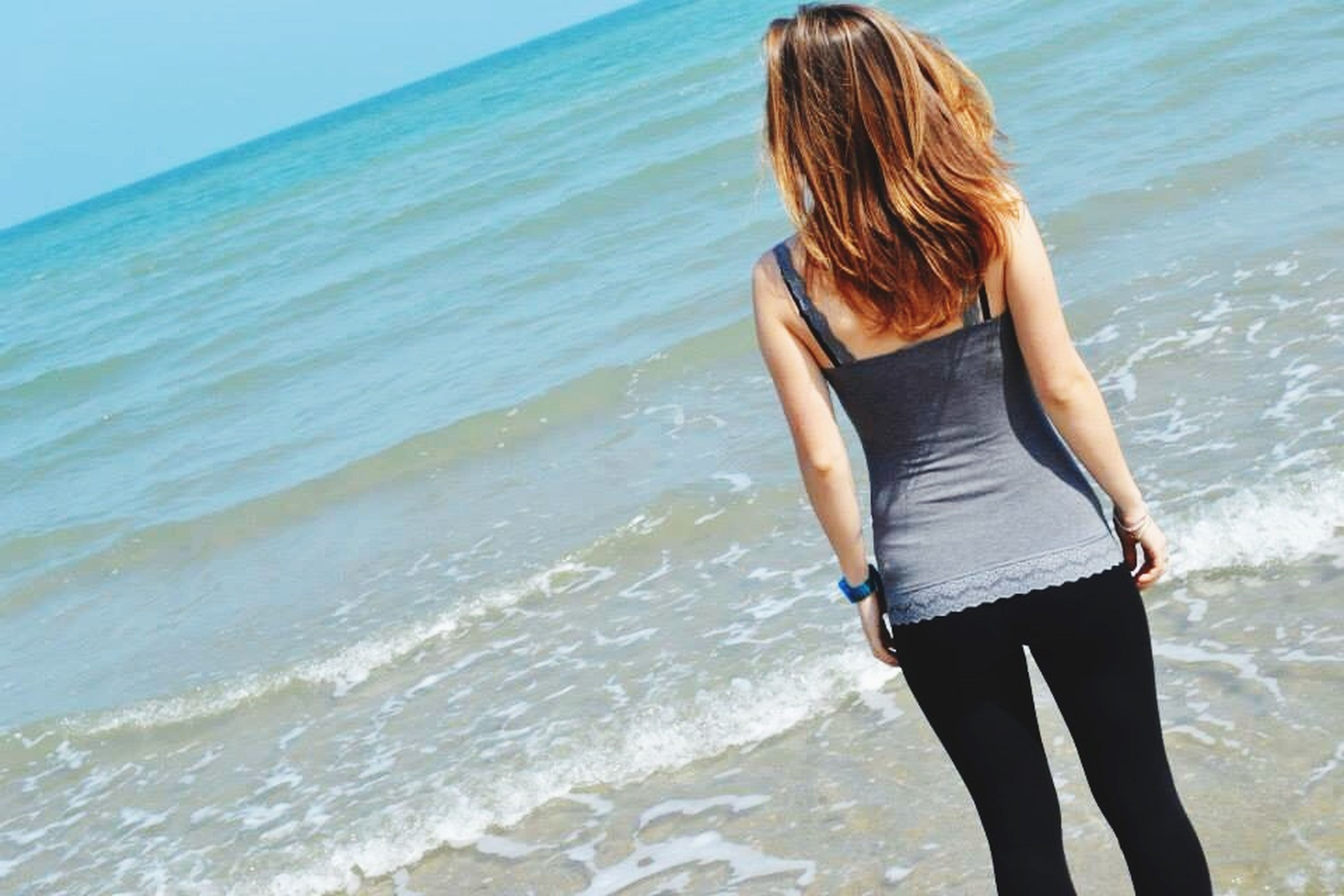 sea, water, beach, leisure activity, lifestyles, rear view, horizon over water, standing, vacations, shore, person, long hair, young women, full length, casual clothing, beauty in nature, nature, tranquility