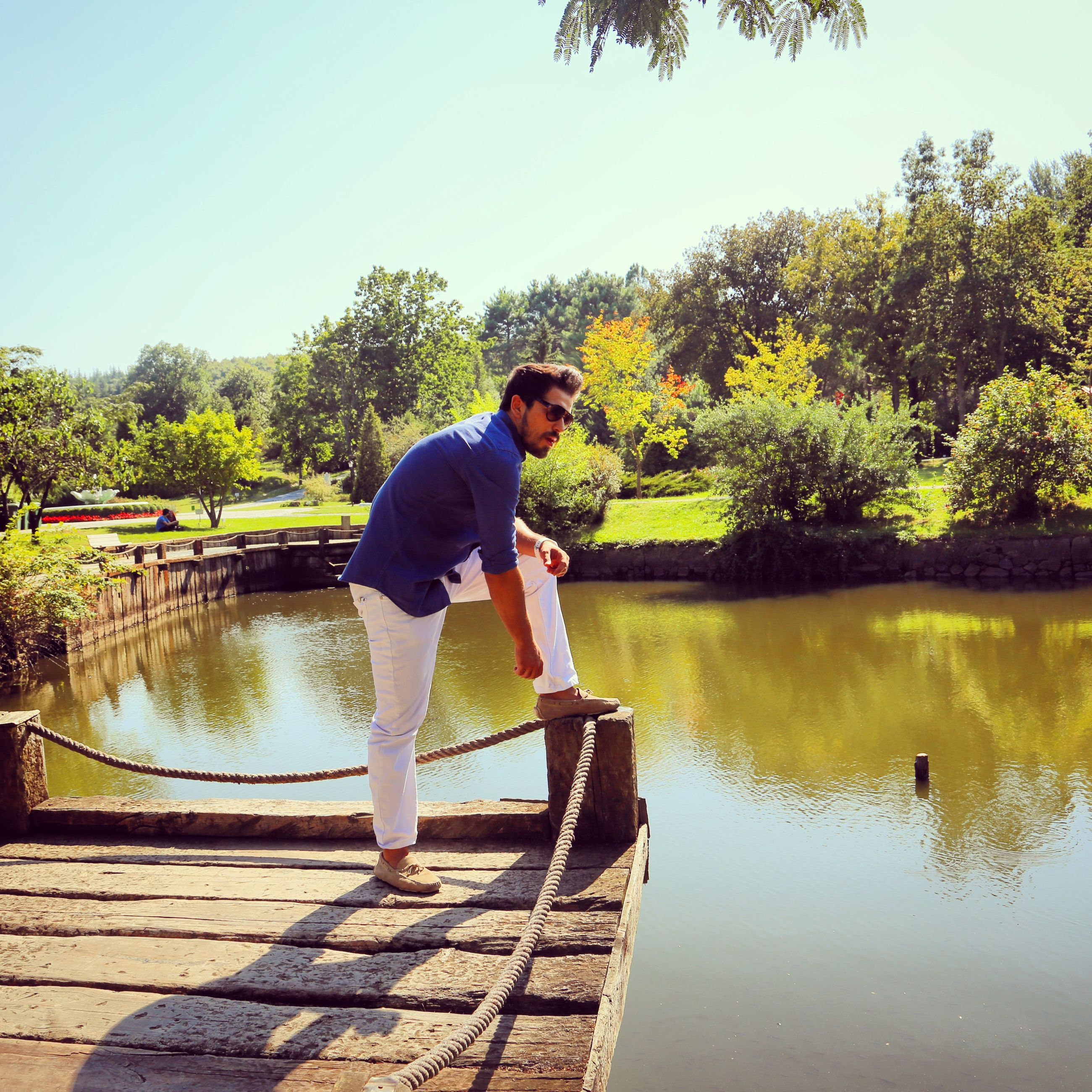 tree, water, full length, lifestyles, casual clothing, leisure activity, clear sky, standing, lake, rear view, young adult, nature, tranquility, river, railing, person, built structure